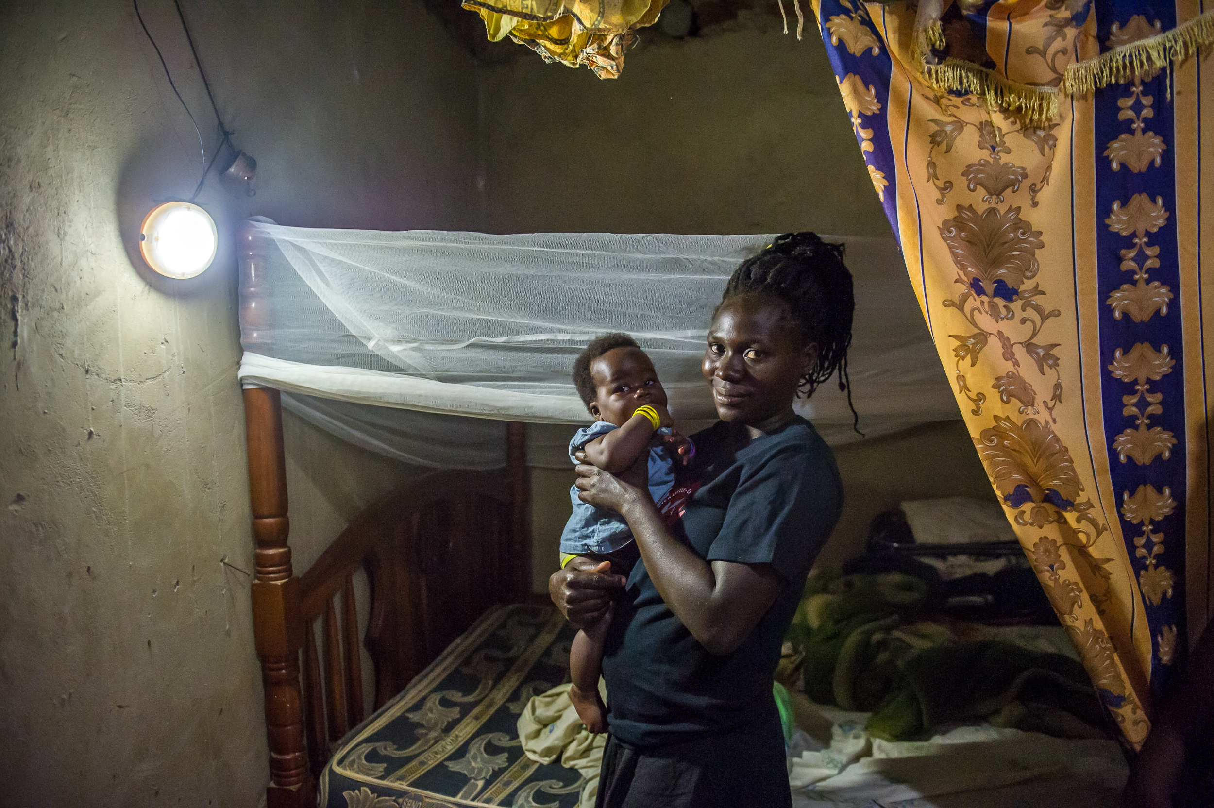 Jane's daughter and grandson in the sleeping area of the home. Jane helps raise her five grandchildren.