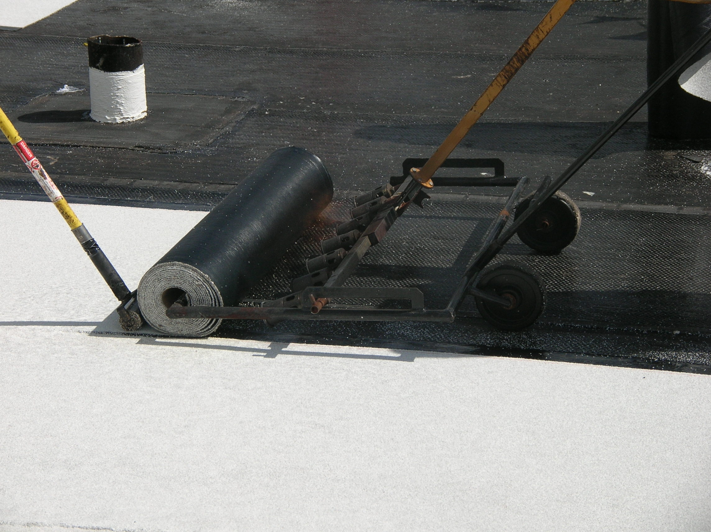 Torch-applying a roll of modified bitumen roofing.