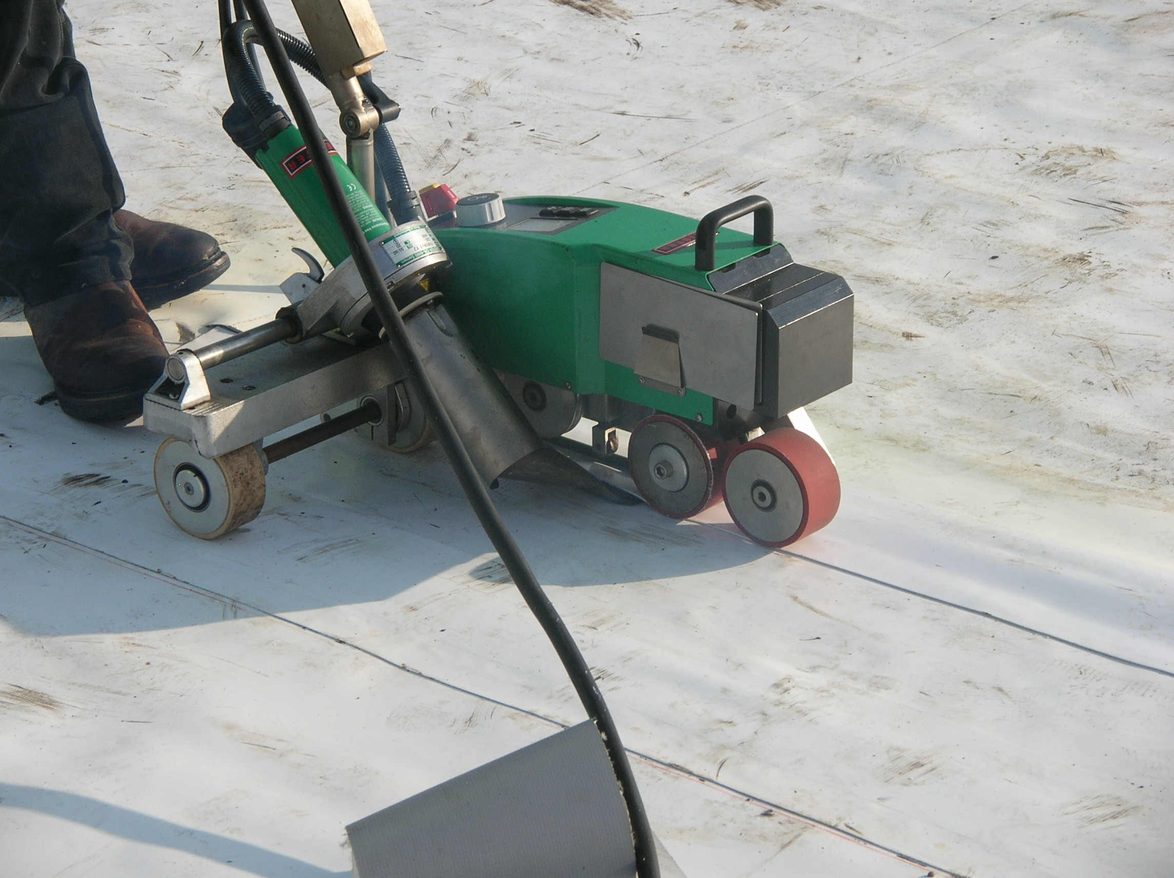 Heat-welding a field seam during the installation of a PVC roof membrane.