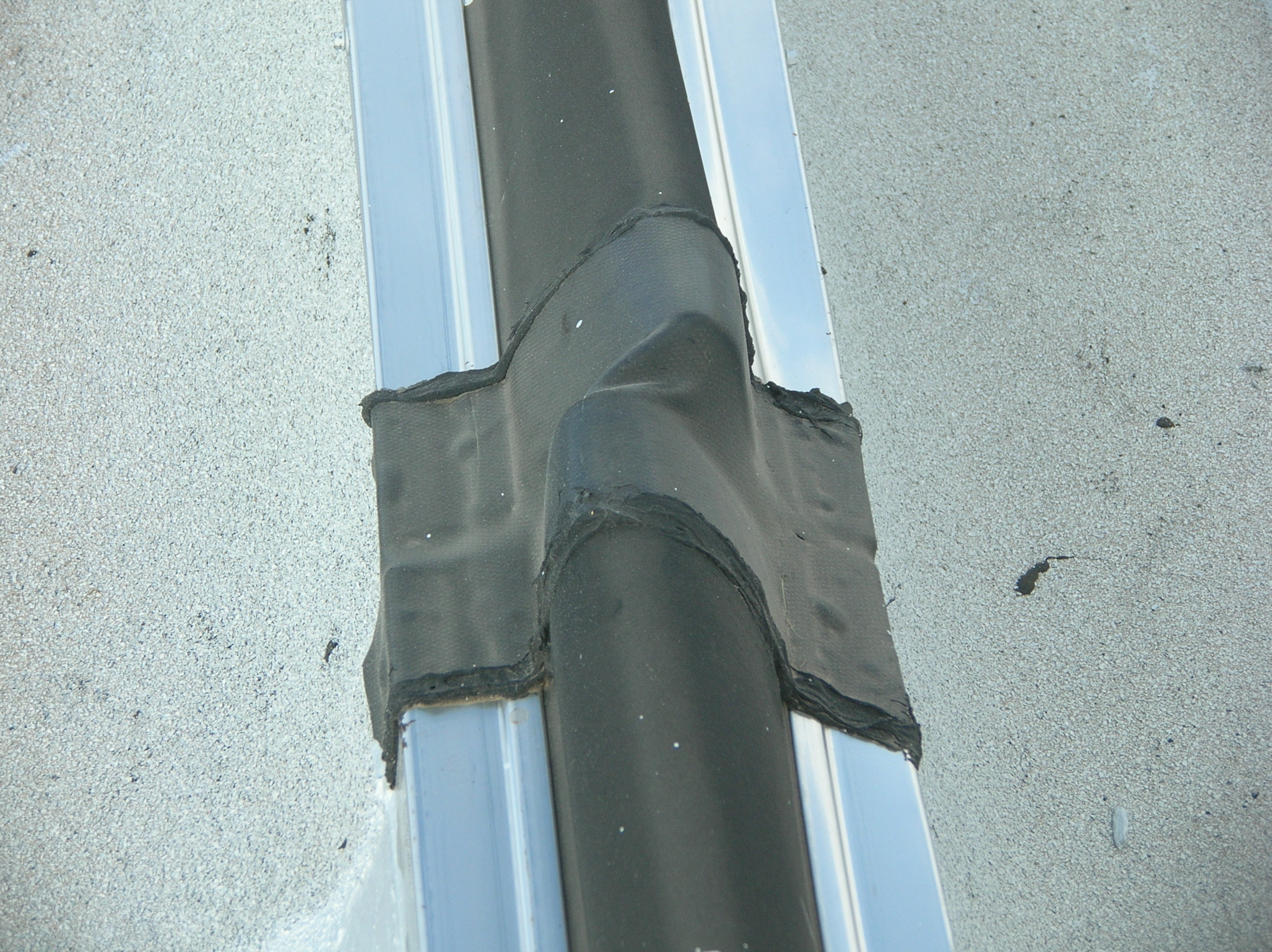 Top view of a curbed expansion joint, showing the joint between sections of the expansion joint cover.