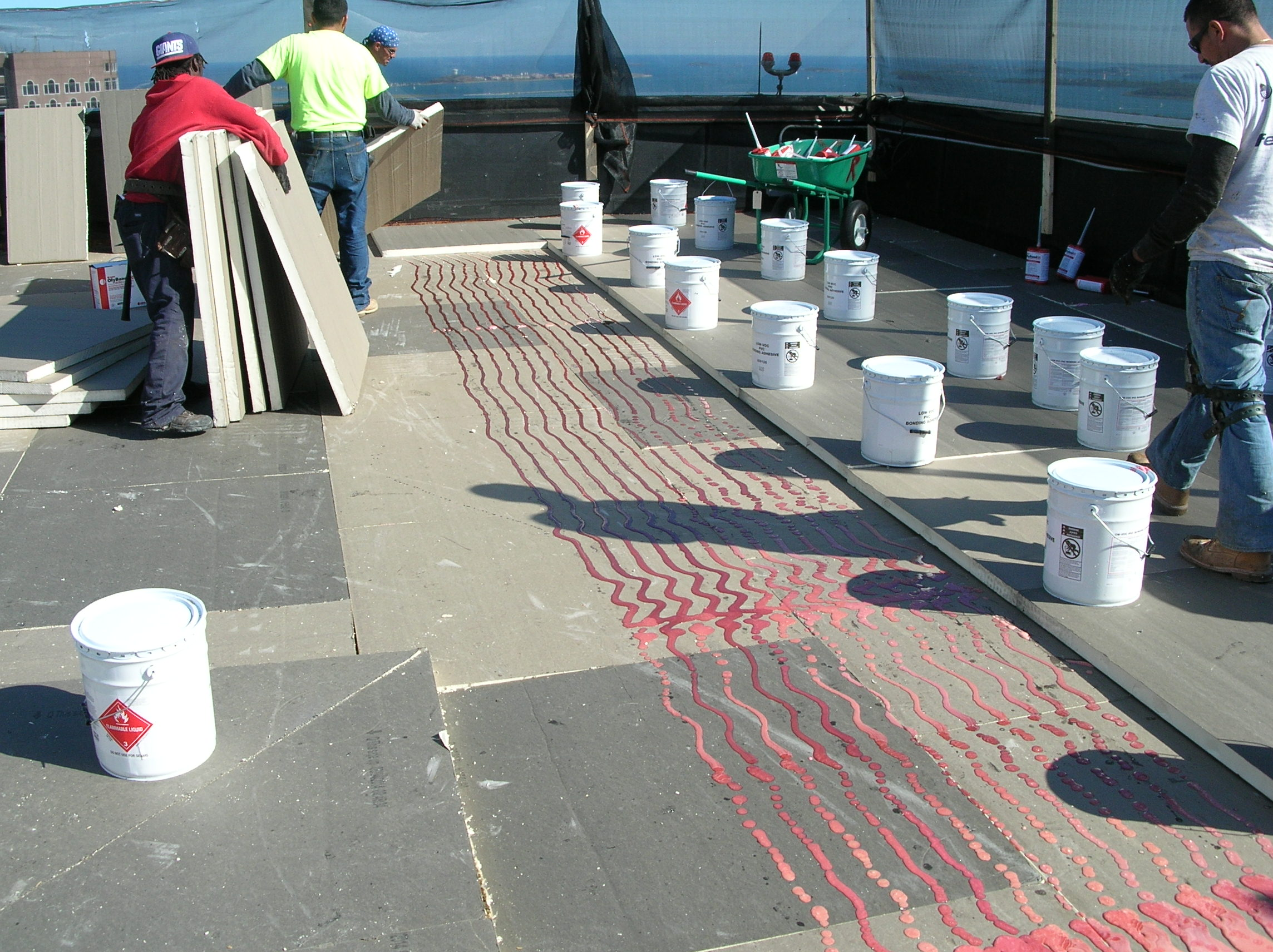 Installing polyisocyanurate insulation boards in adhesive during a roof installation.