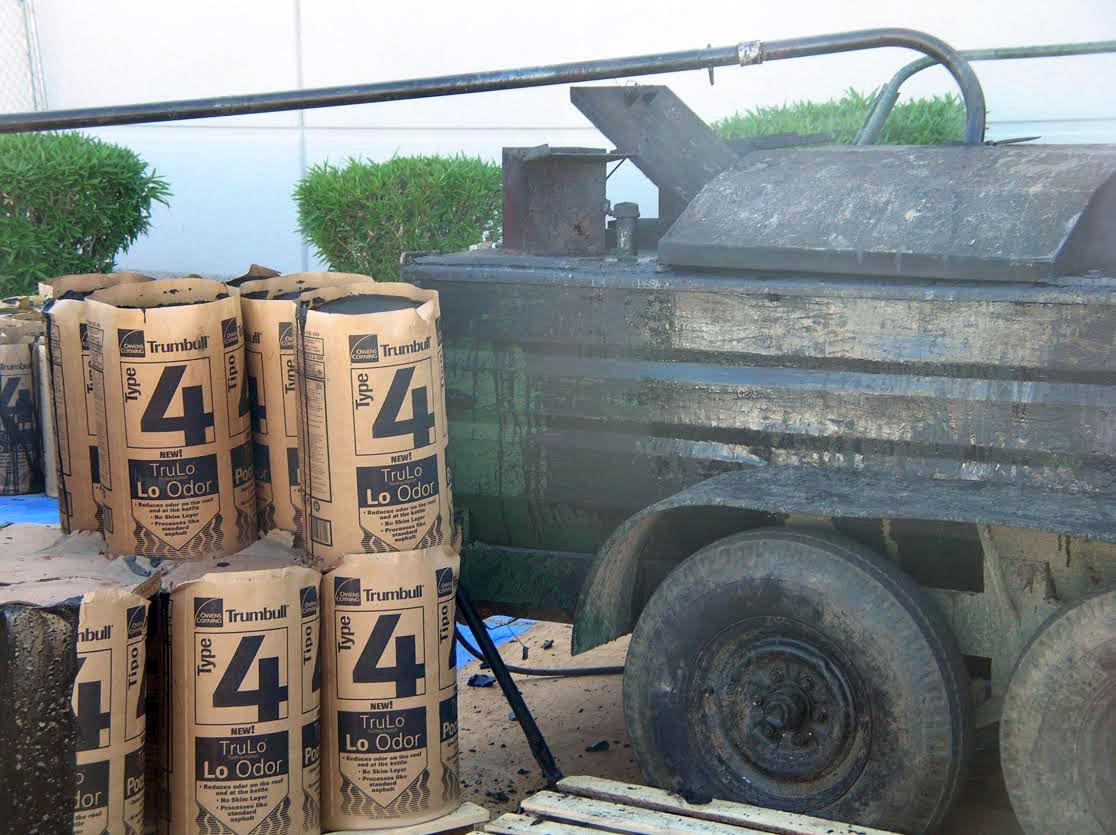 Kegs of Type 4 roofing asphalt next to an asphalt kettle.