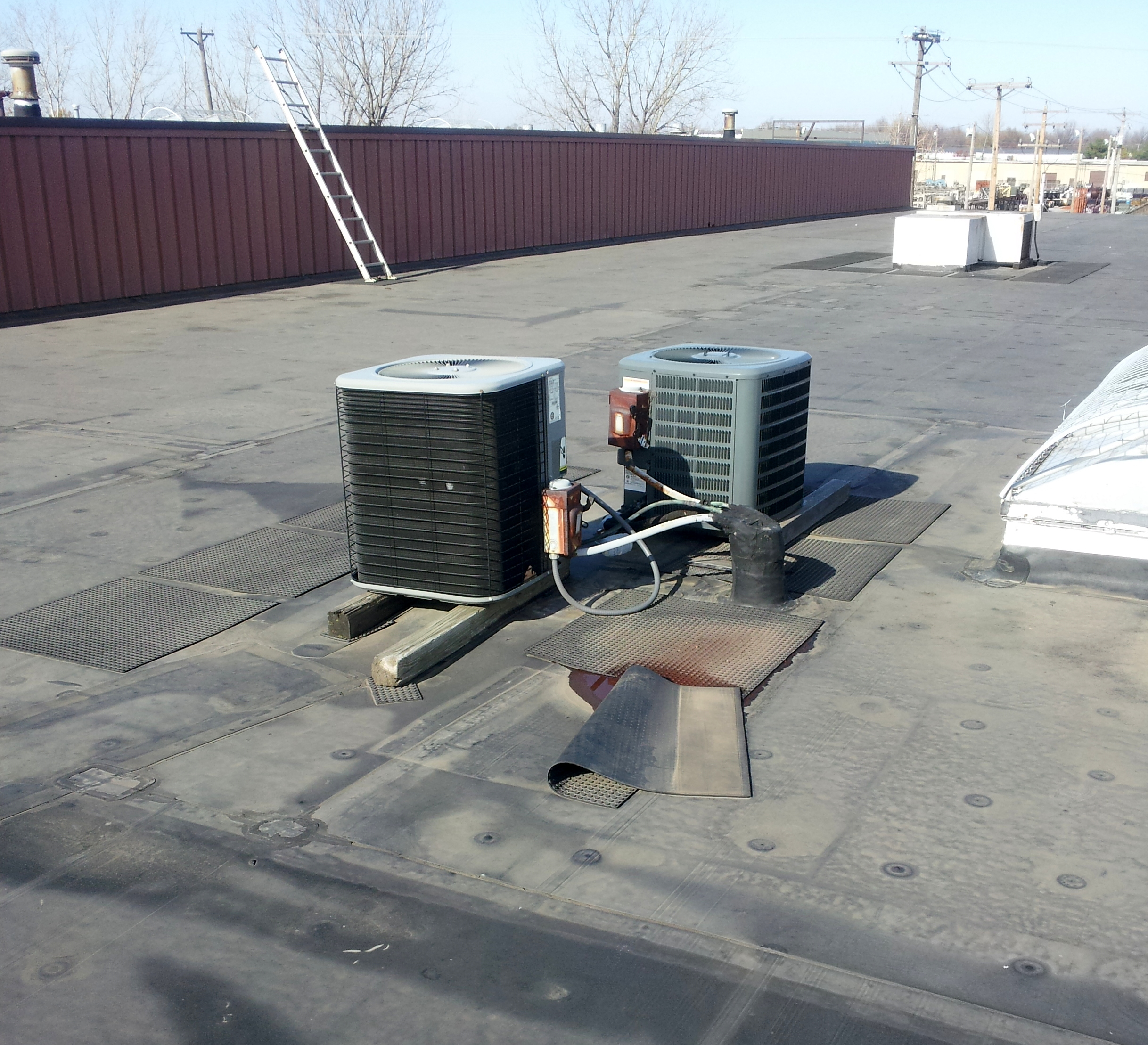 Two small rooftop units on sleeper supports.