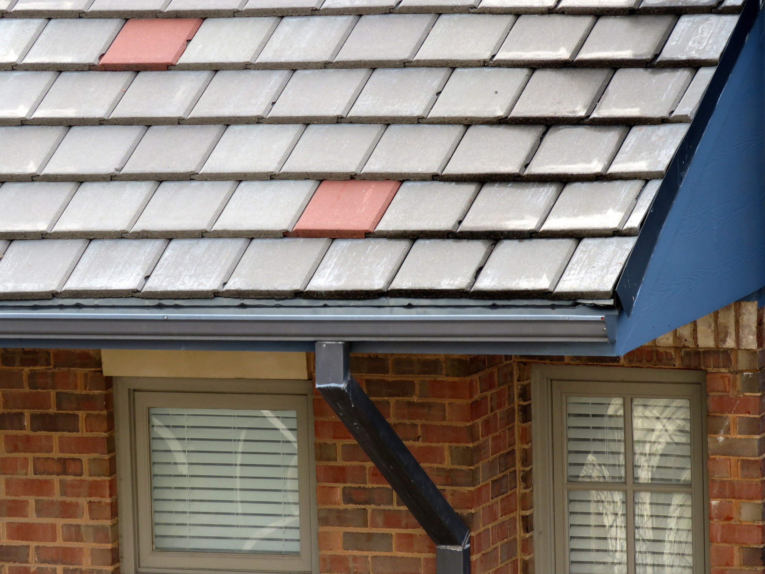 K-style gutter with downspout on a steep-slope roof.