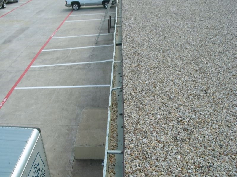 Gutter on a gravel-surfaced built-up roof. Removing loose gravel from the gutters is a common maintenance item with this type of roof.