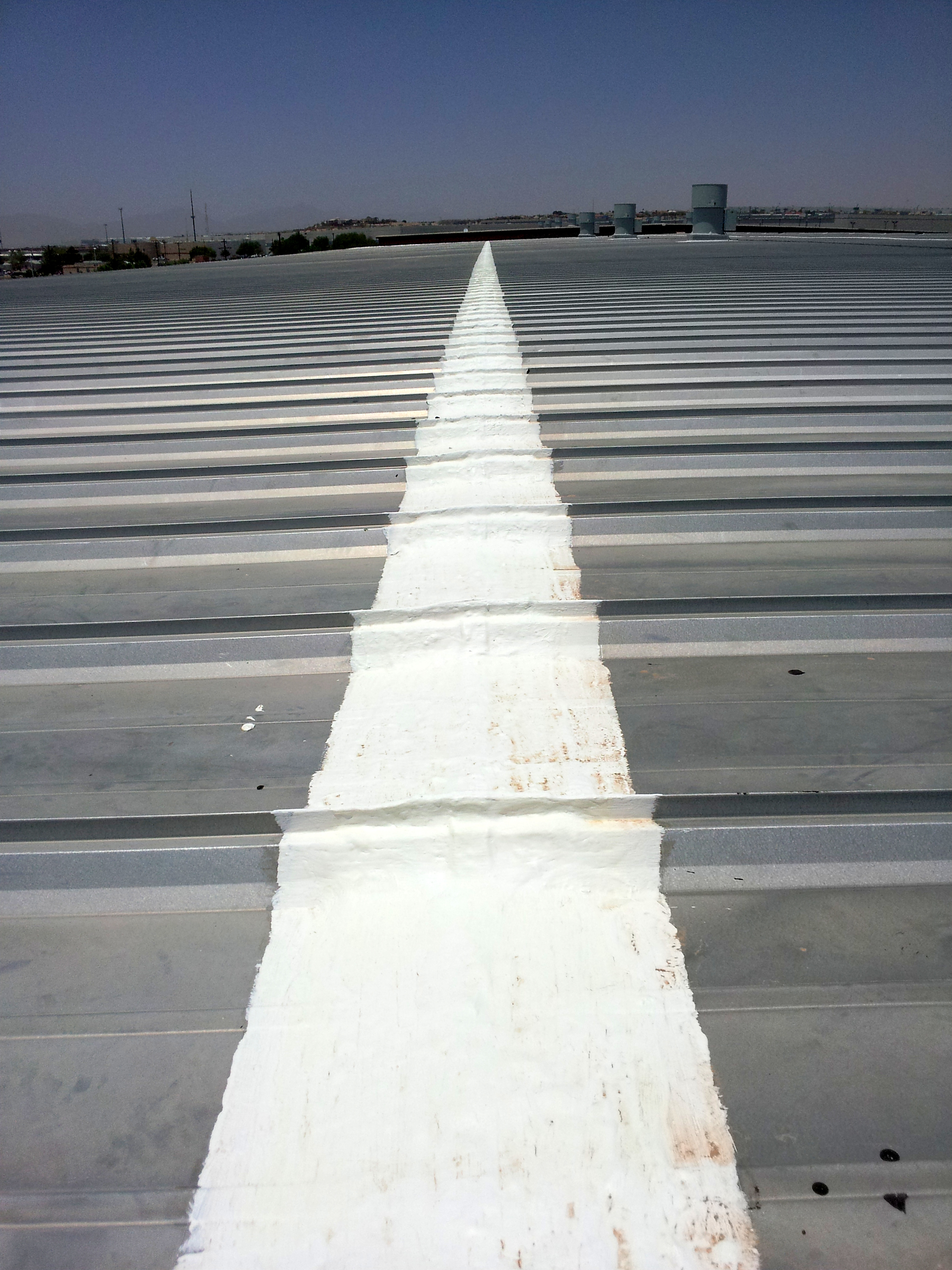 A white, elastomeric, fabric-reinforced roof coating has been applied to the panel laps on this structural metal panel roof. The original sealant within the laps had deteriorated. this isn't the way the manufacturer recommends the problem be addressed, but it's far cheaper and effective enough.