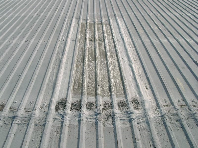 An aged ribbed fiberglass skylight on a metal panel roof. Not to be stepped on.