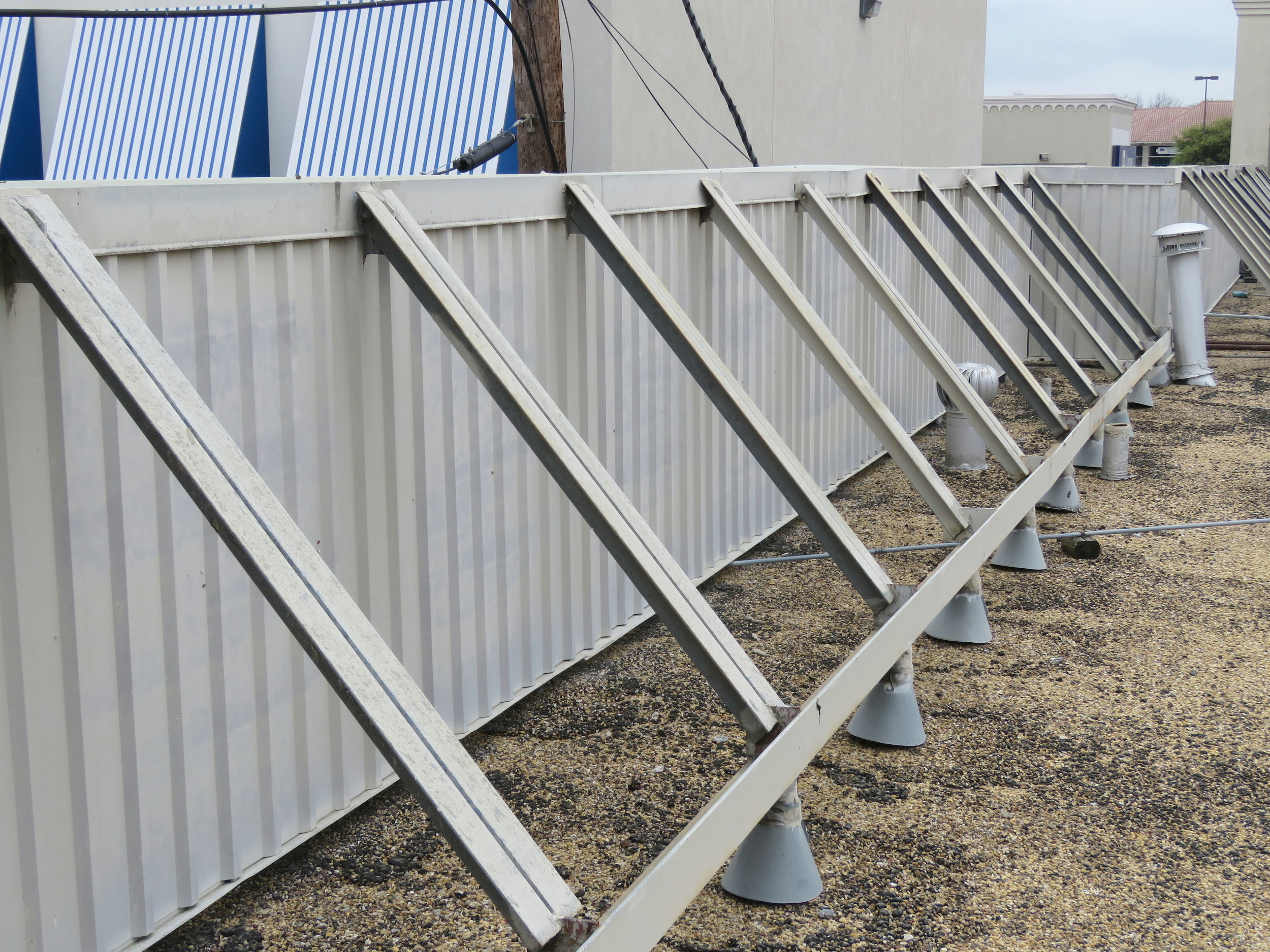 Metal panel wall serving as both a rooftop equipment screen and a parapet wall.