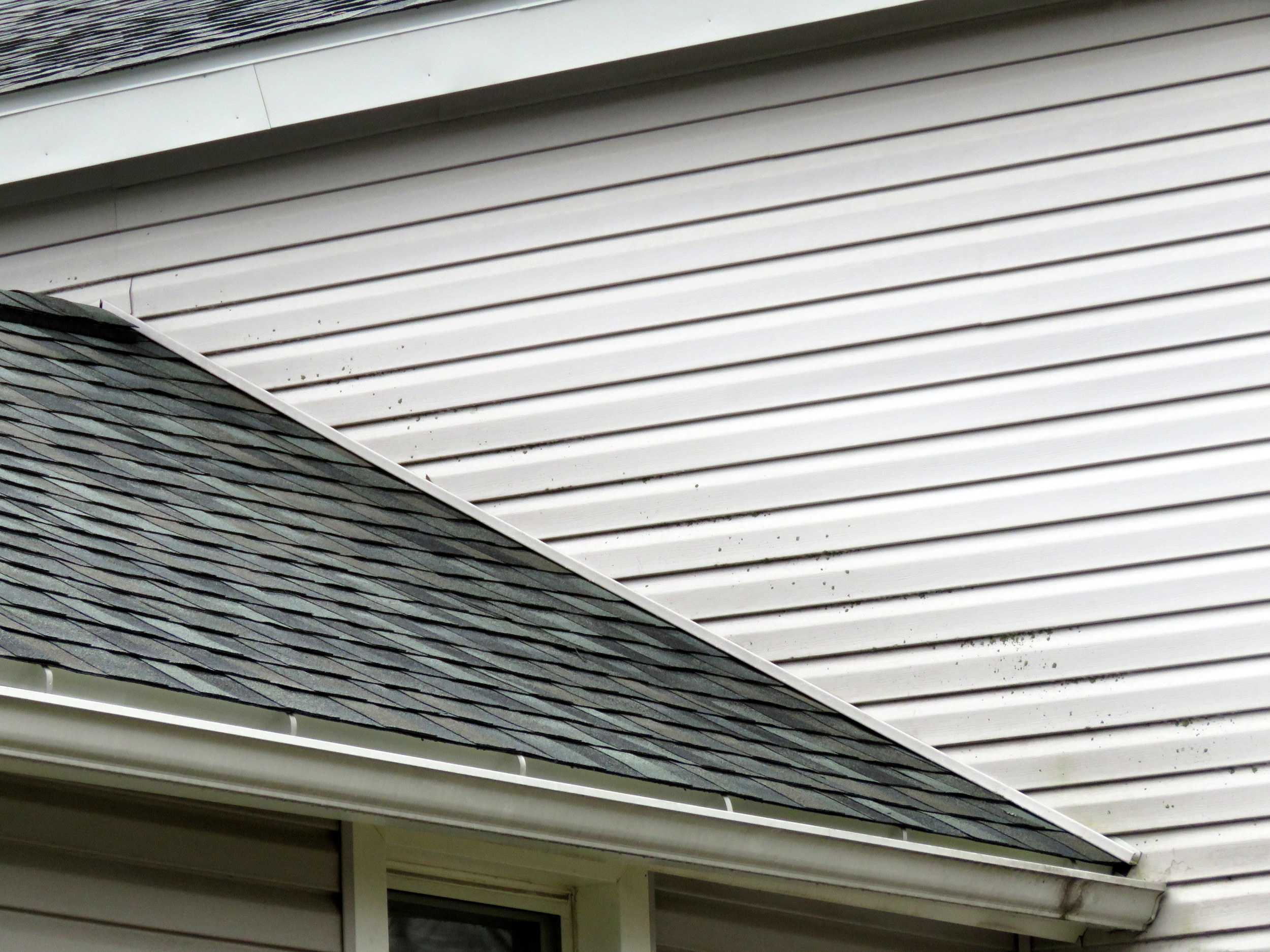 Aluminum siding meets an asphalt shingle roof.