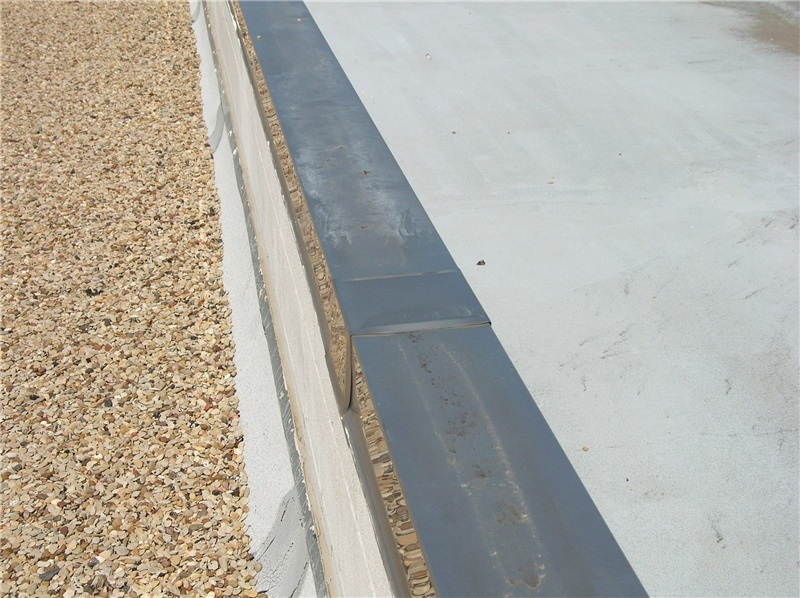20-year-old stainless steel parapet wall coping. (Note the reflection of the gravel in the side of the coping.)