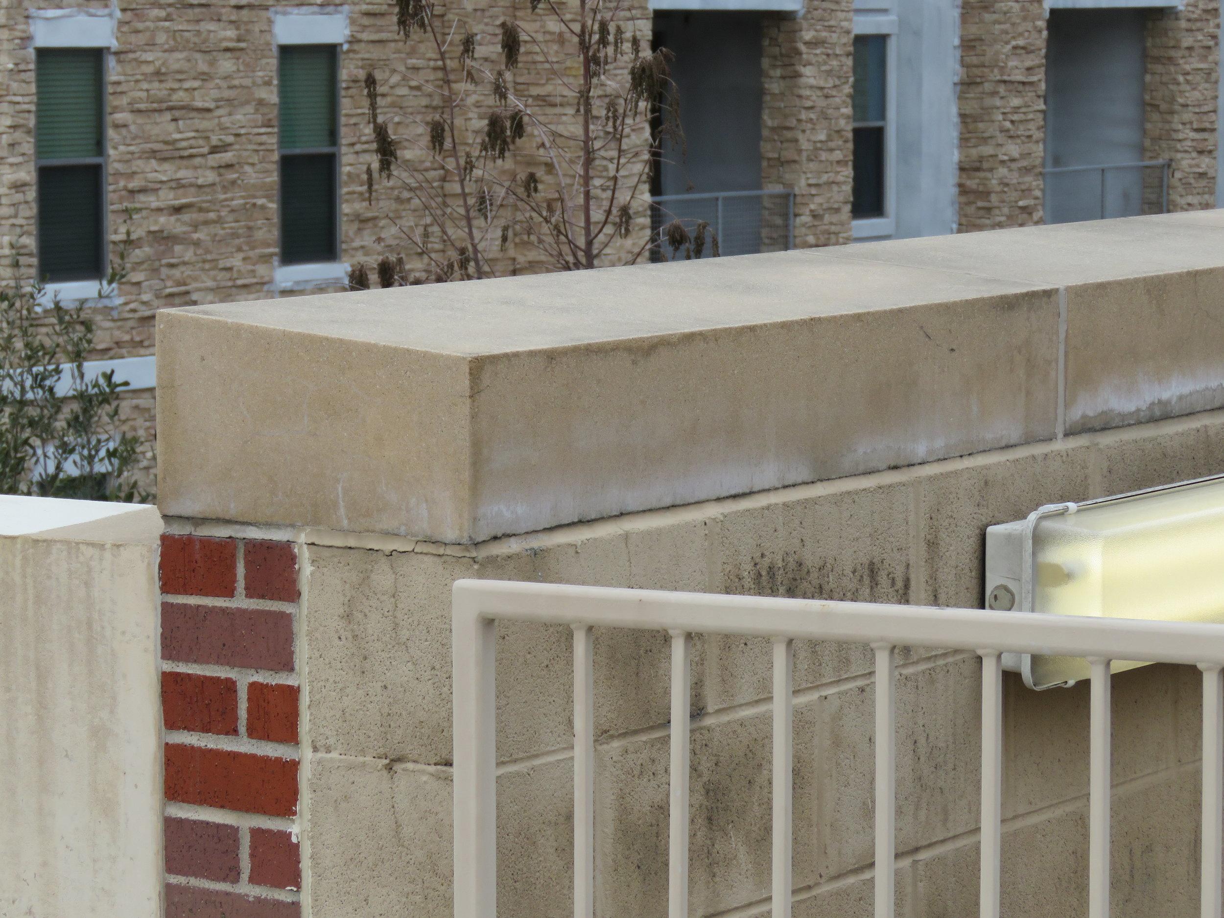 Single-slant pre-cast concrete parapet wall coping.