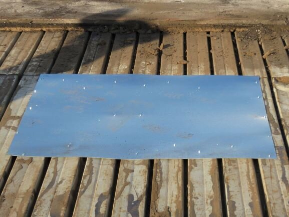 A piece of 24-gauge galvanized steel used to patch a rusted area of steel roof deck.