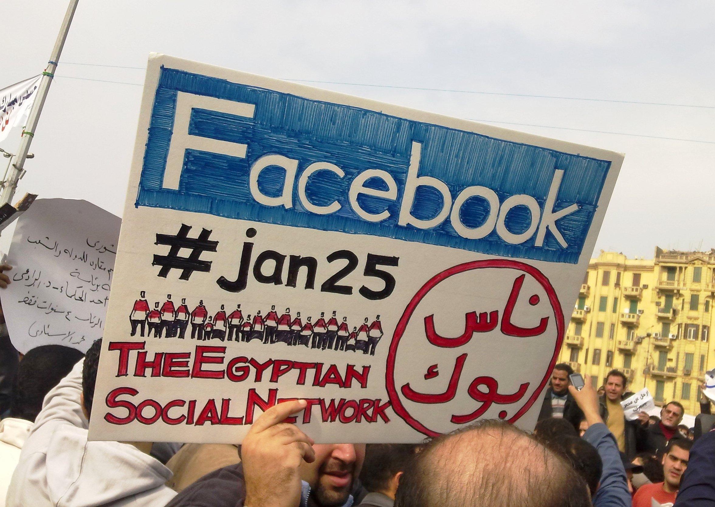 Un hombre sostiene un cartel con el hastagh de Twitter #jan25 (enero 25) y el logo de Facebook durante las protestas en El Cairo en 2011