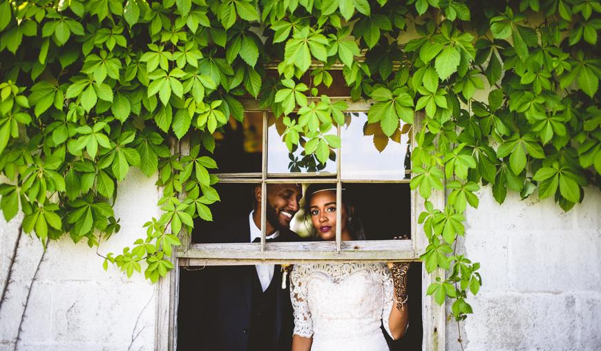 014 gorgeous bride looking out an old broken window.jpg