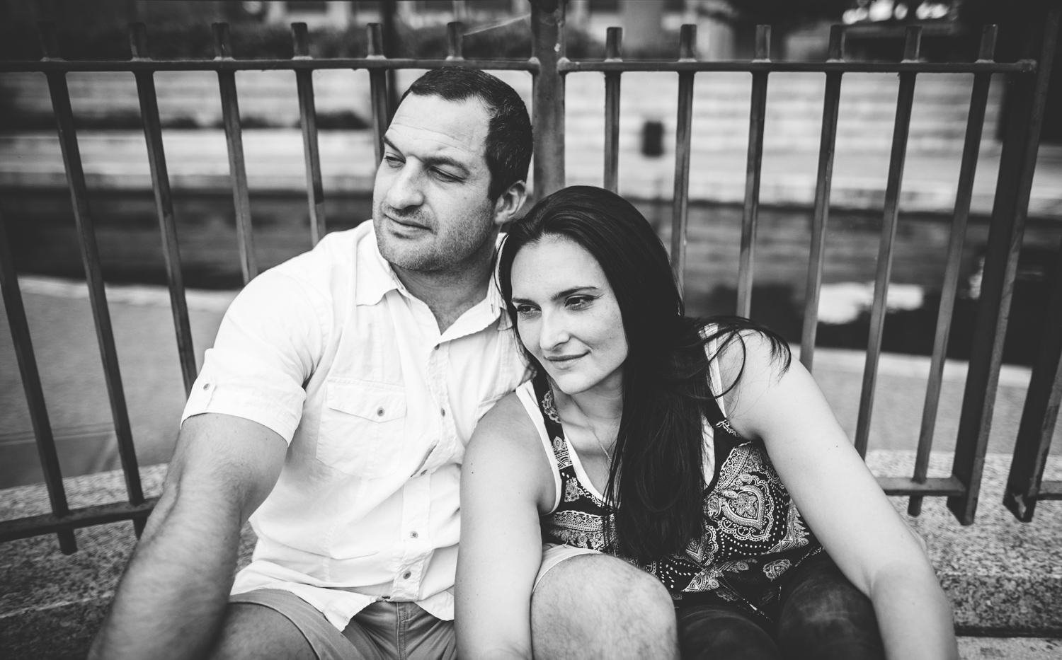 003 black and white portrait of couple sitting down looking off into distance.jpg