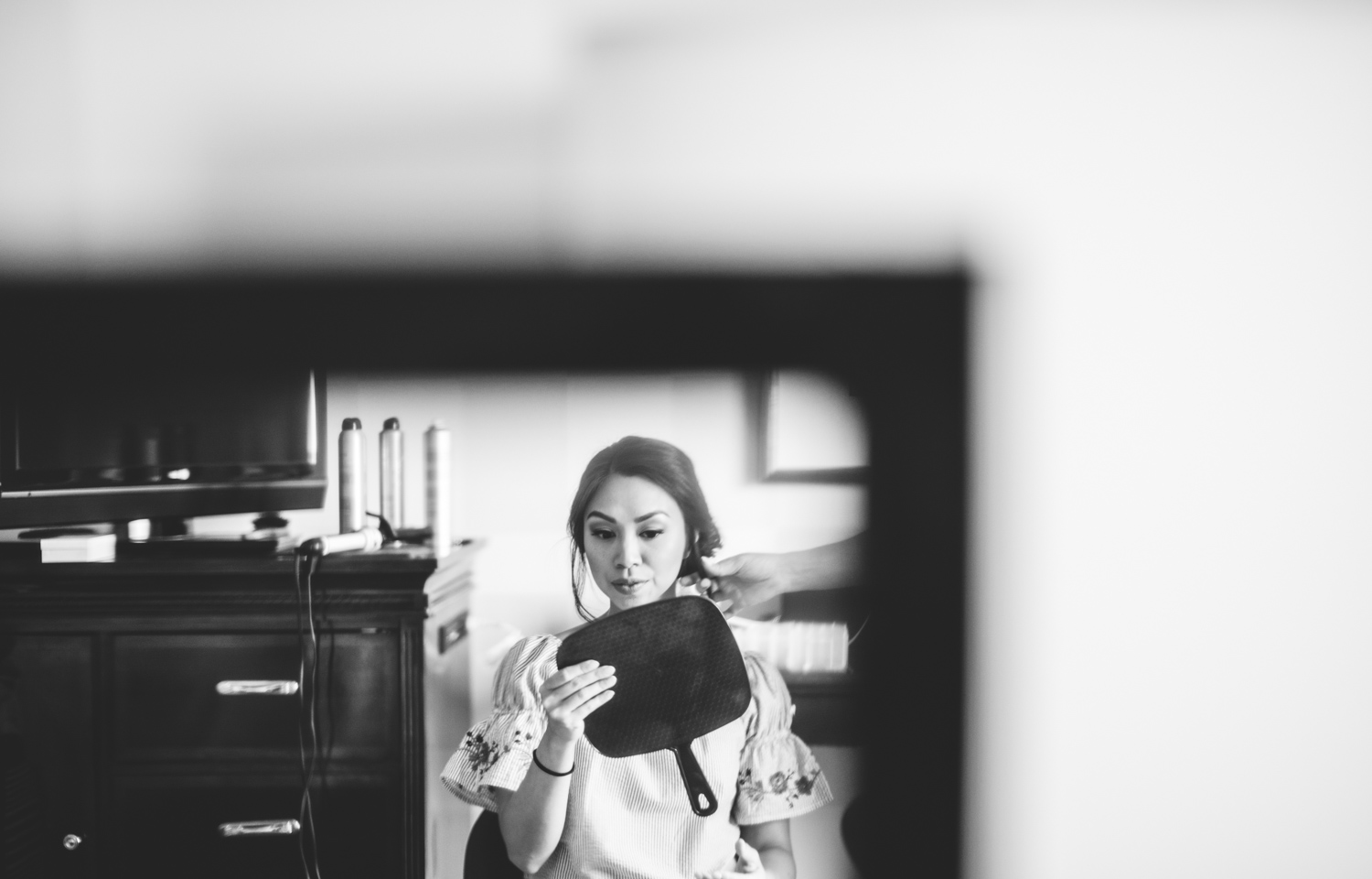 002 bride looking into mirror while getting ready black and white.jpg