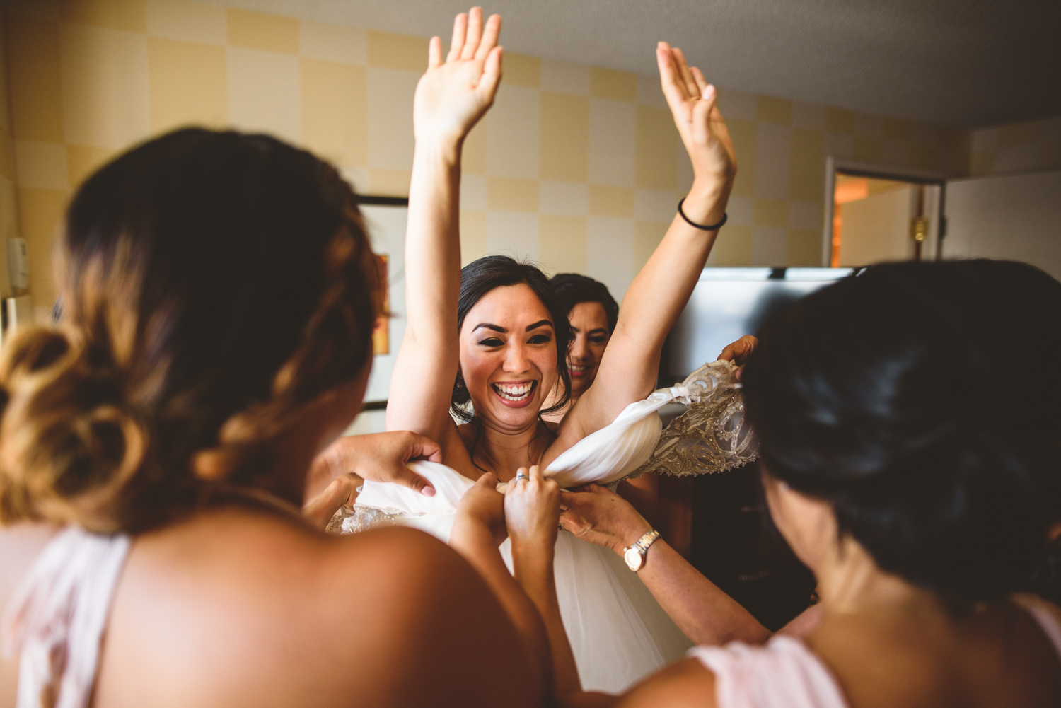 005 bride laughing as bridesmaids help her into wedding dress.jpg