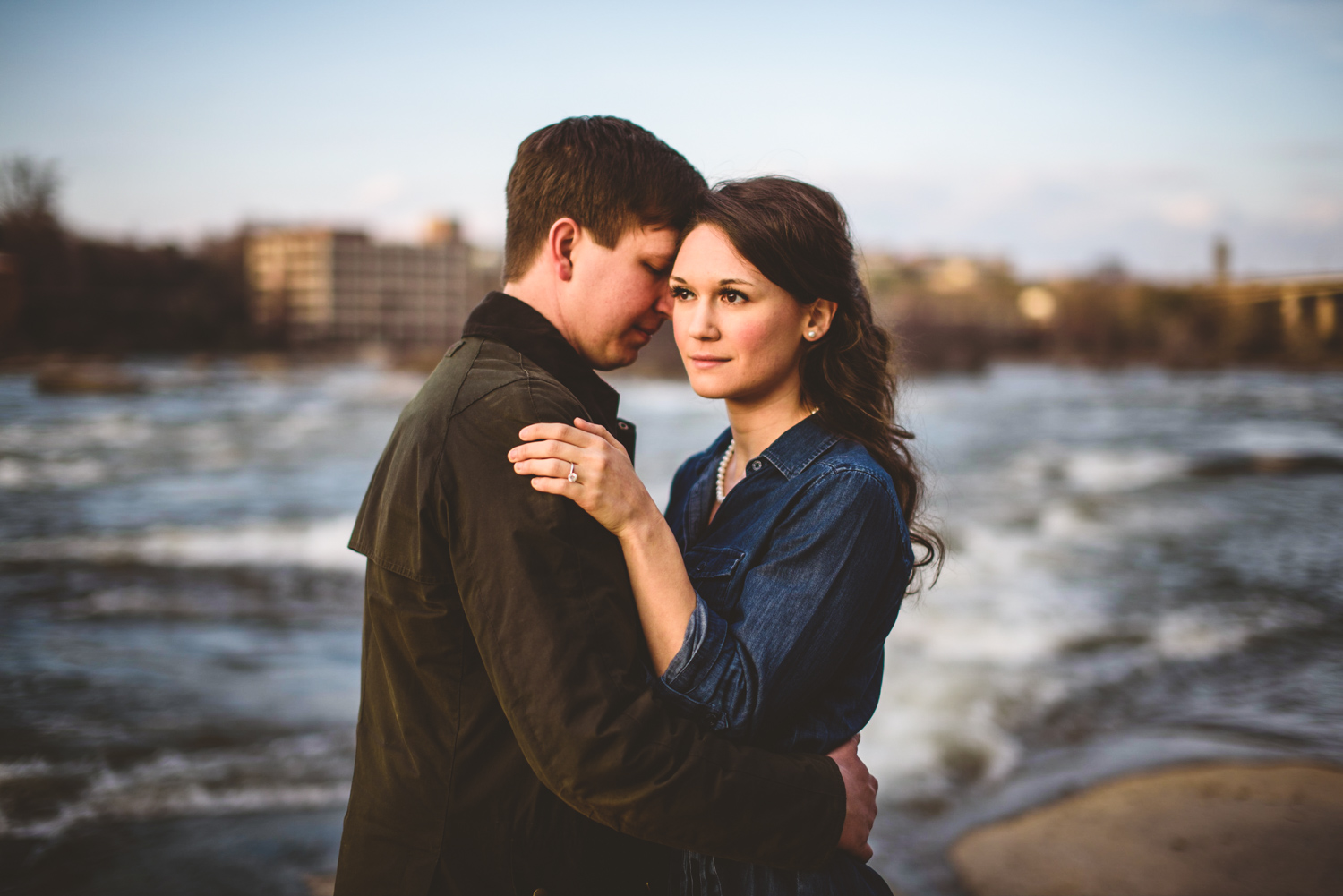 004 - woman looking into sunset while man holds her engagement session.jpg