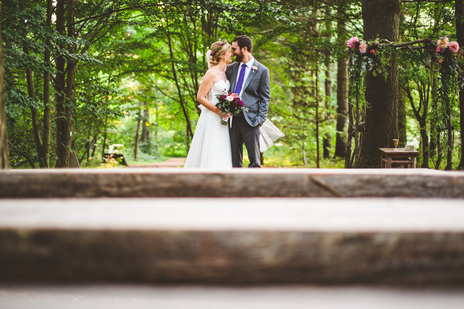 014 - portrait of bride and groom in forest with wooden seats in foreground.jpg