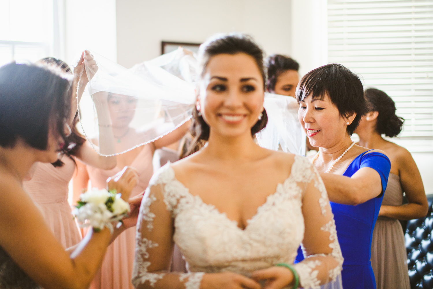 003 bride's mother smiles as she helps her daughter into dress.jpg