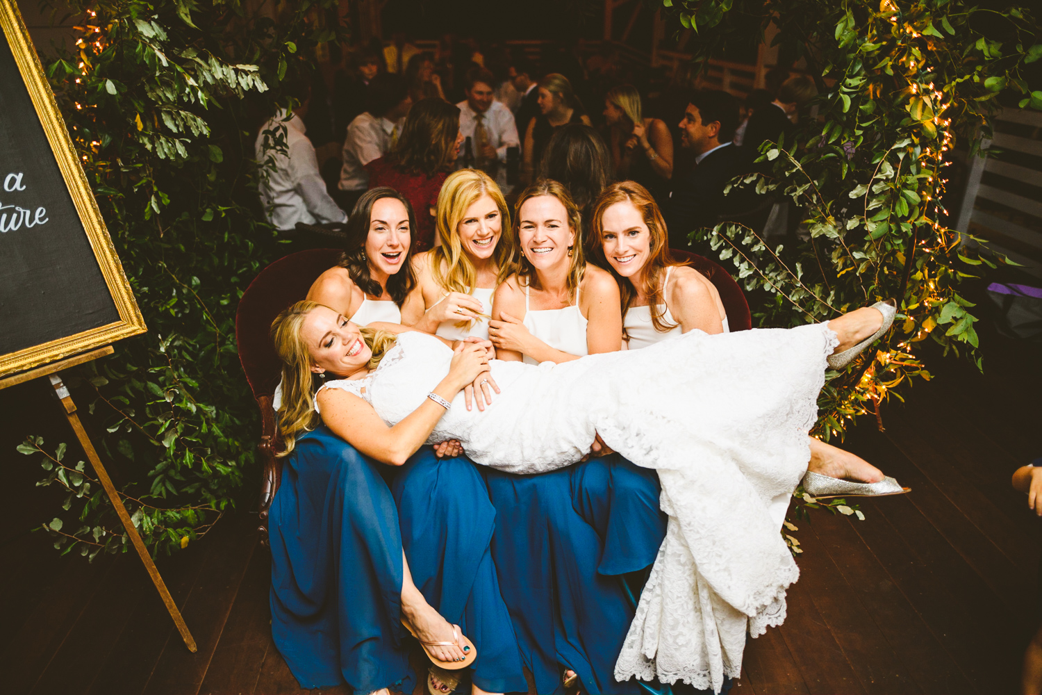 014 - bridesmaids hold up the bride for a group photo.jpg