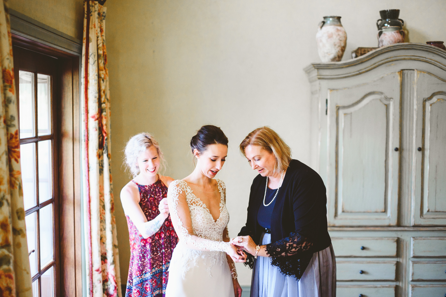 011 - mother of the bride and maid of honor help bride put on wedding dress.jpg