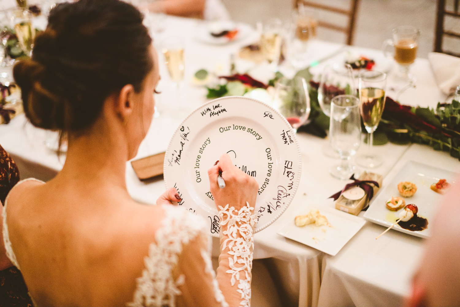 033 - bride signs a guestbook decorative plate that will go into their home.jpg