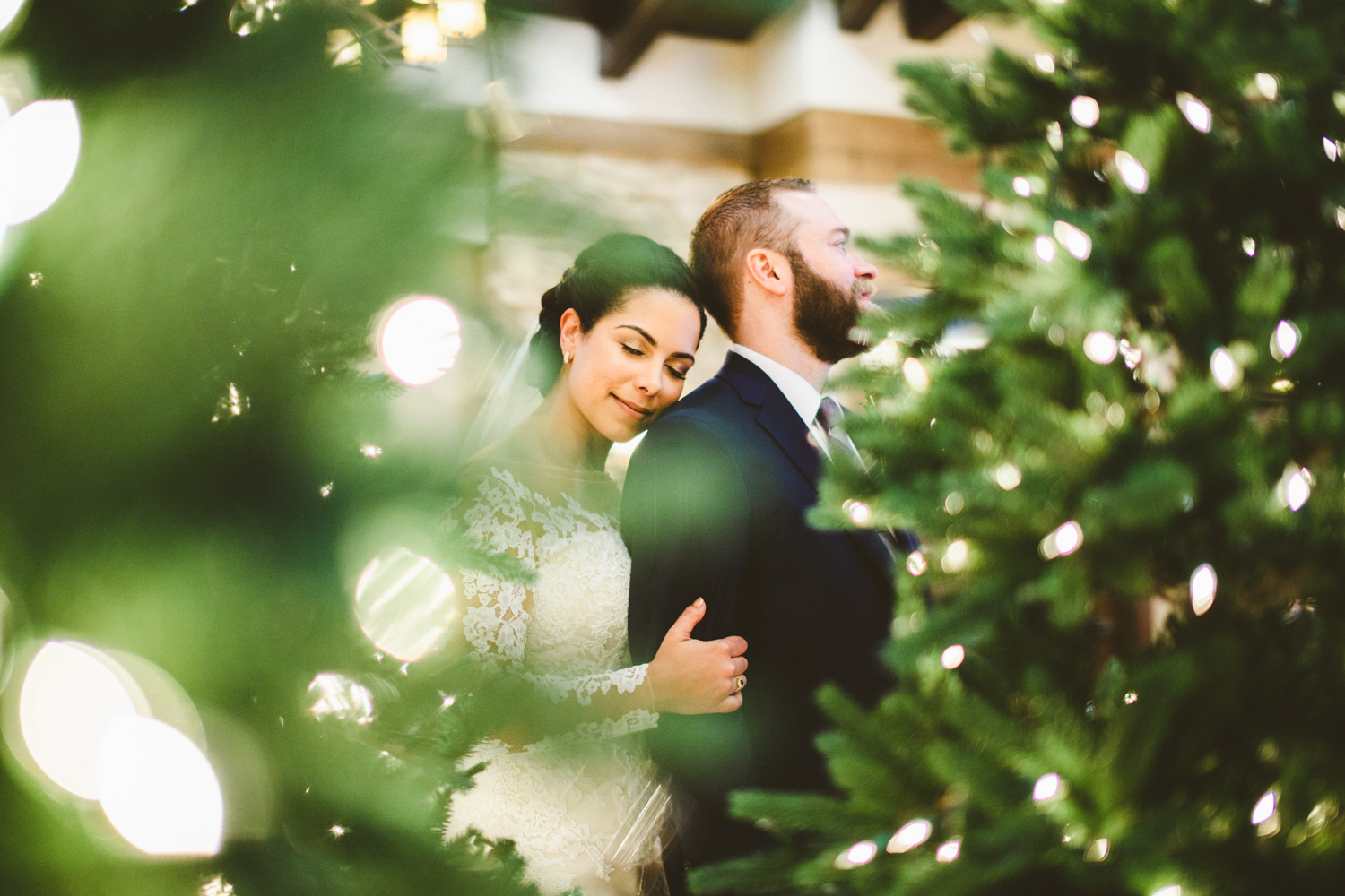 035a - gorgeous portrait of bride and groom with christmas lights in the foreground and the bride's cheek on groom's shoulder.jpg