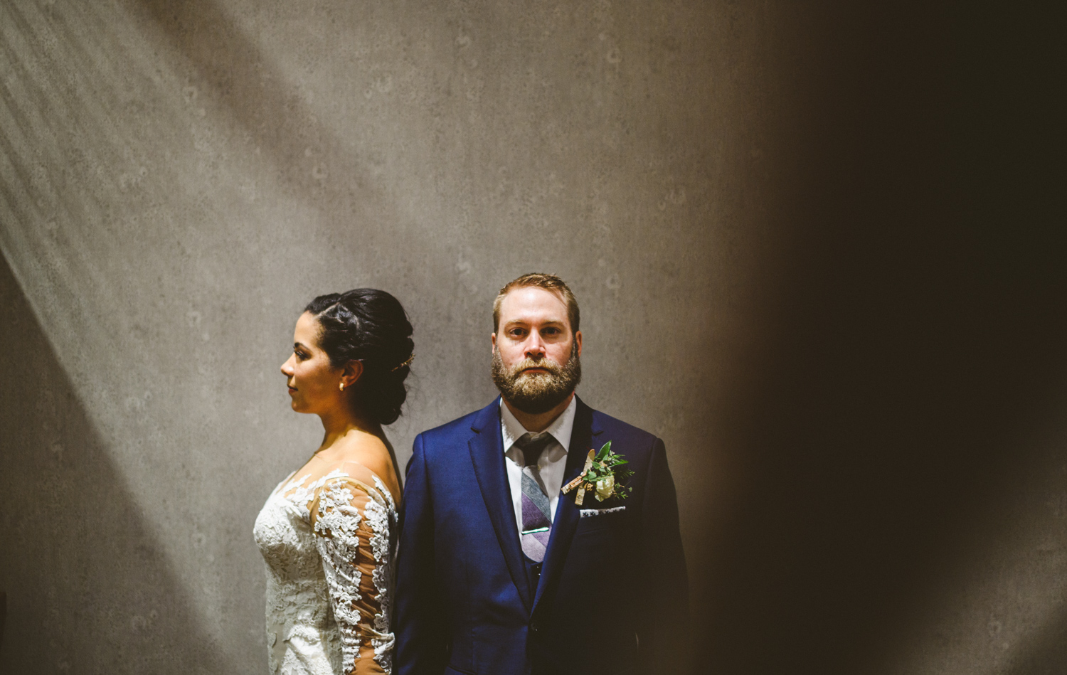 048 - creative portrait of bride and groom with groom looking at the camera and light beaming down from above night portrait.jpg