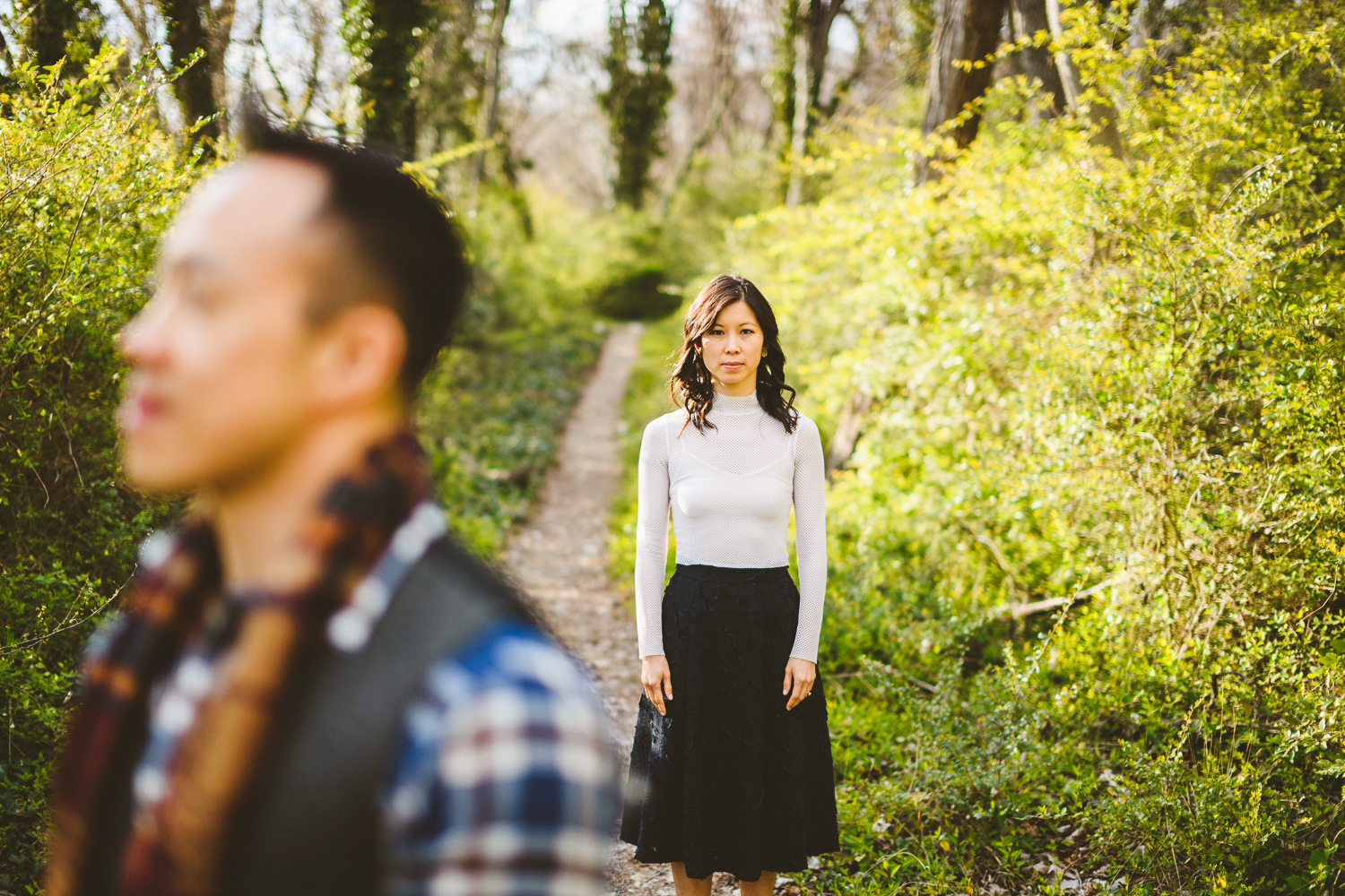 008 - woman looking into camera with man out of focus in foreground and a path leading off in the distance.jpg