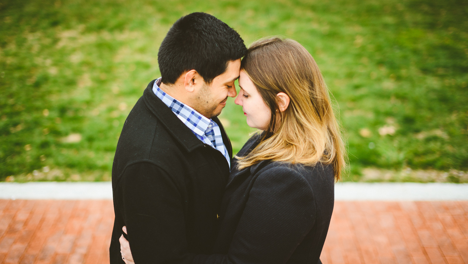 002 - couple embracing with green grass and red bricks behind them.jpg