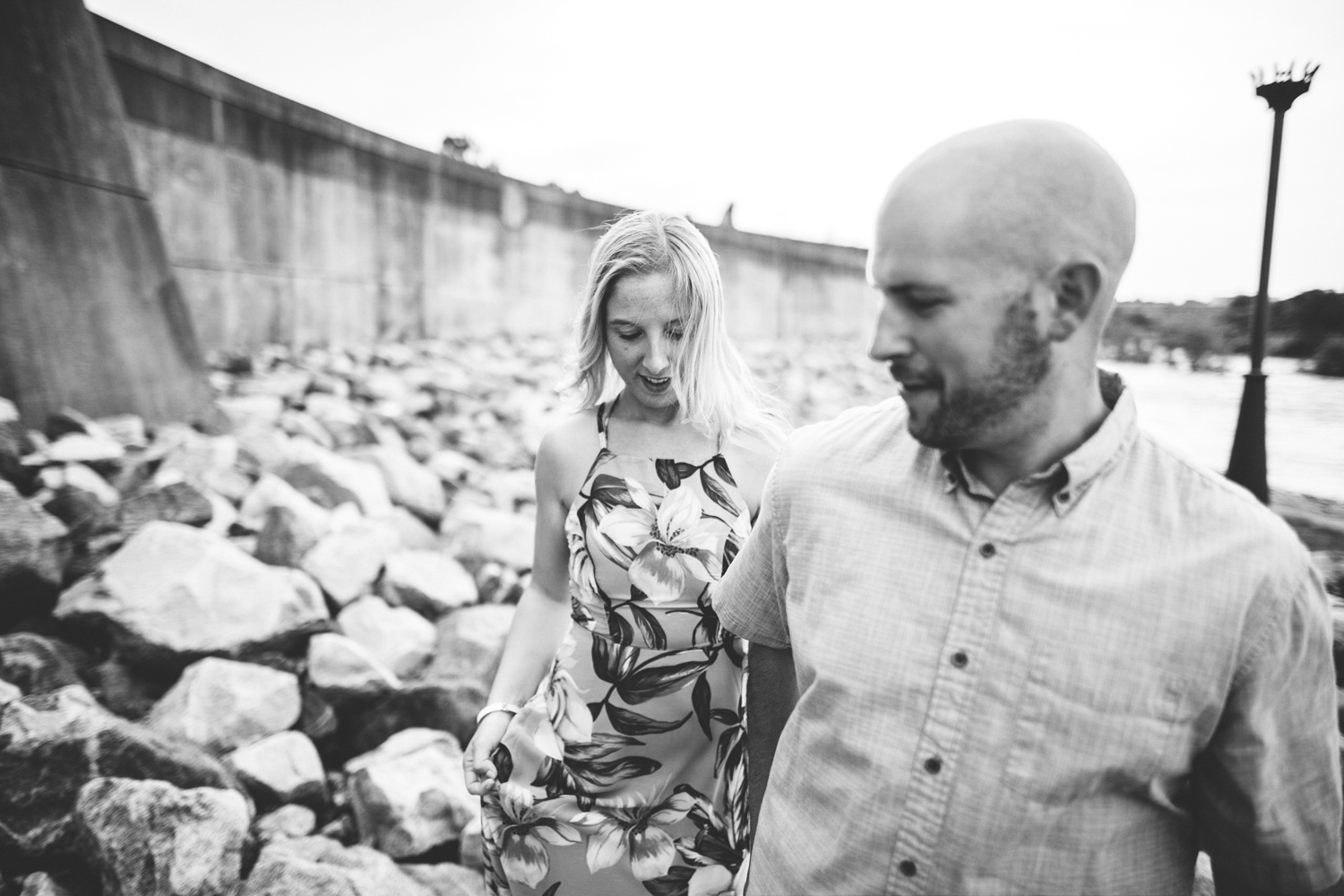 008 - man holds woman's hand and walks along the rocks near the james river during an engagement session.jpg