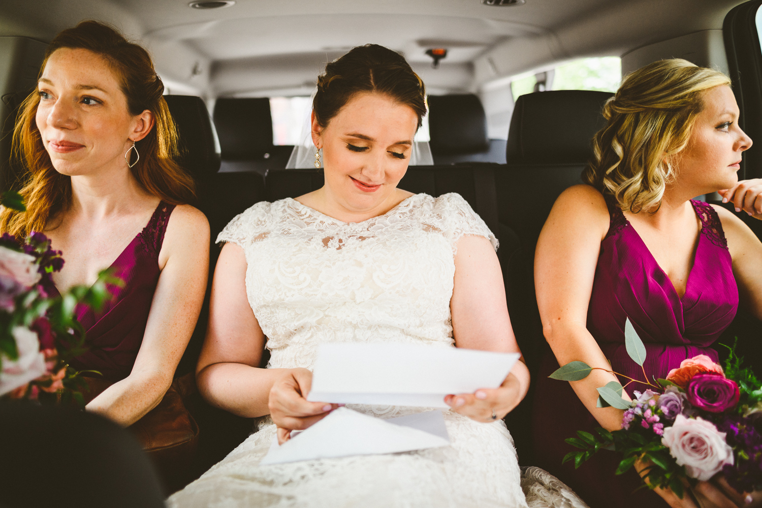 003 - bride reads a note from her husband to be on the way to the chapel to get married.jpg