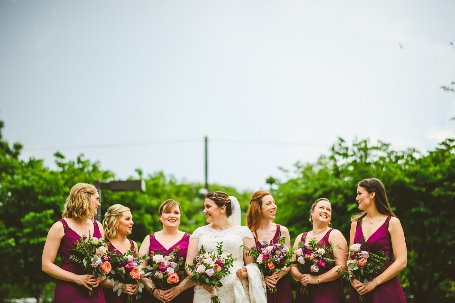 005 - bride laughing with bridesmaids in front of green trees.jpg
