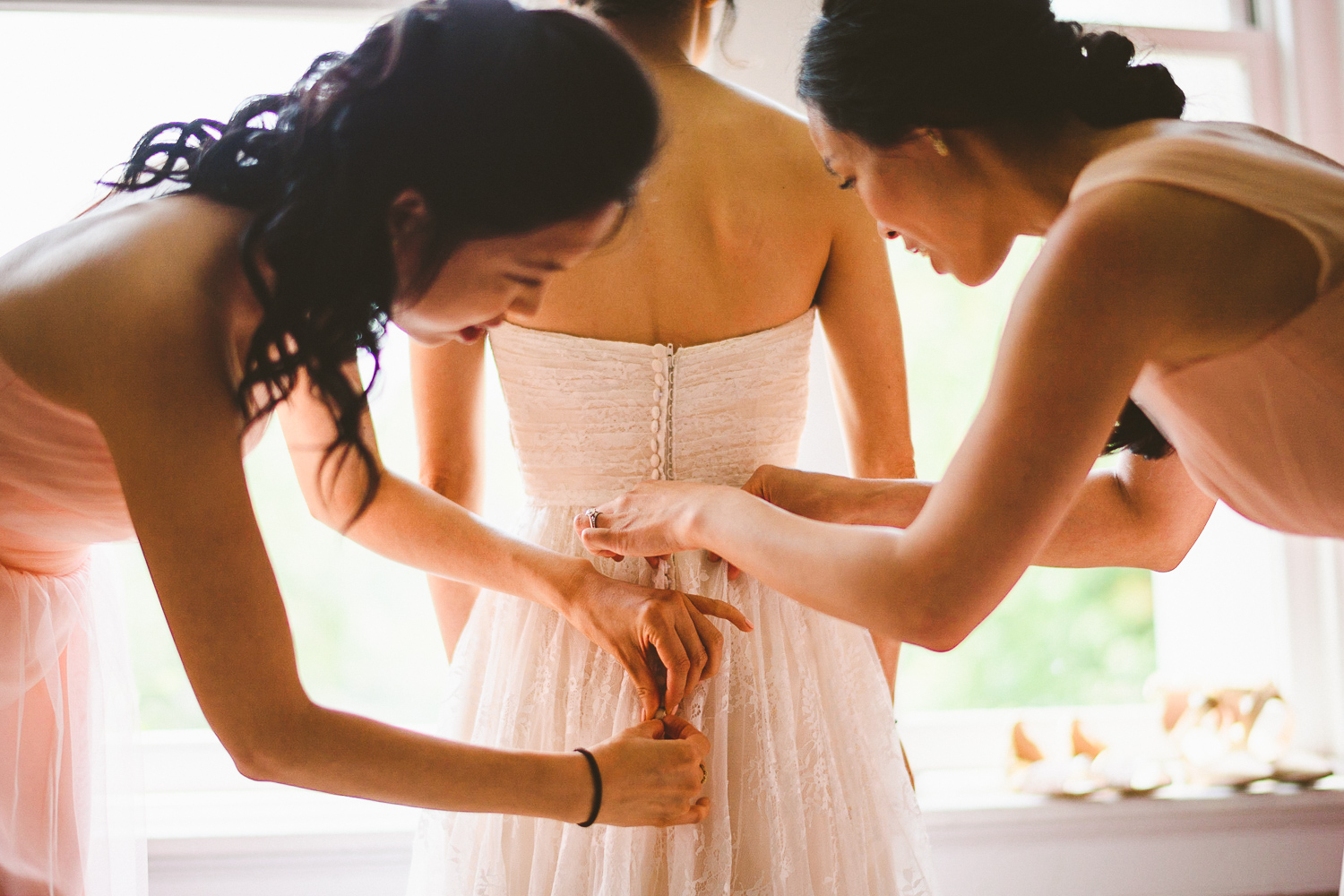 006 - bridesmaids helping the bride button up her wedding dress.jpg