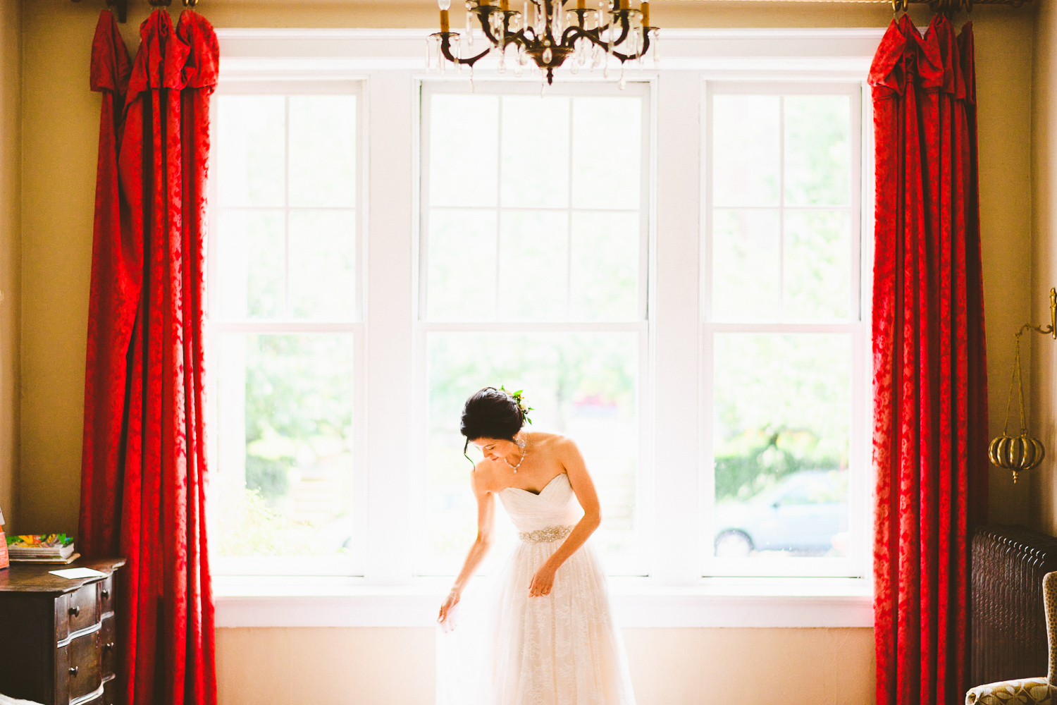 010 - portrait of the bride in front of window with beautiful red curtains.jpg