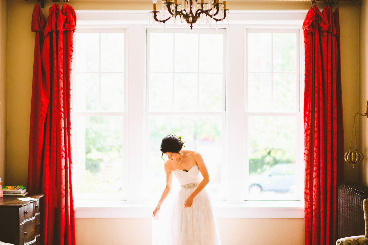 050 - bride adjusting her dress in front of big picture window with red curtains.jpg