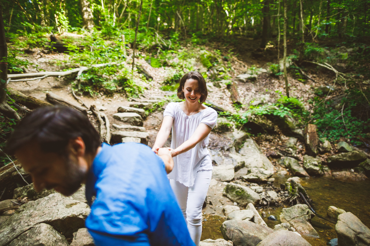 005 - man leads woman over creek rocks at their engagement session.jpg