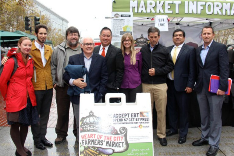 Celebrating the passage of nutrition incentive matching legislation AB 1321 at Heart of the City Farmers Market in September. From left: Christina Oatfield, Eli Zigas, Peter Ruddock, Michael Dimock, Assemblymember Phil Ting, Kate Creps, Martin Bourque, Xavier Morales, Allen Moy. Photo: Doris Meier