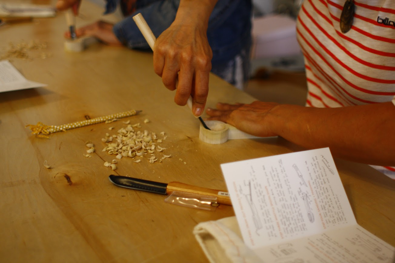 A student carving her spoon