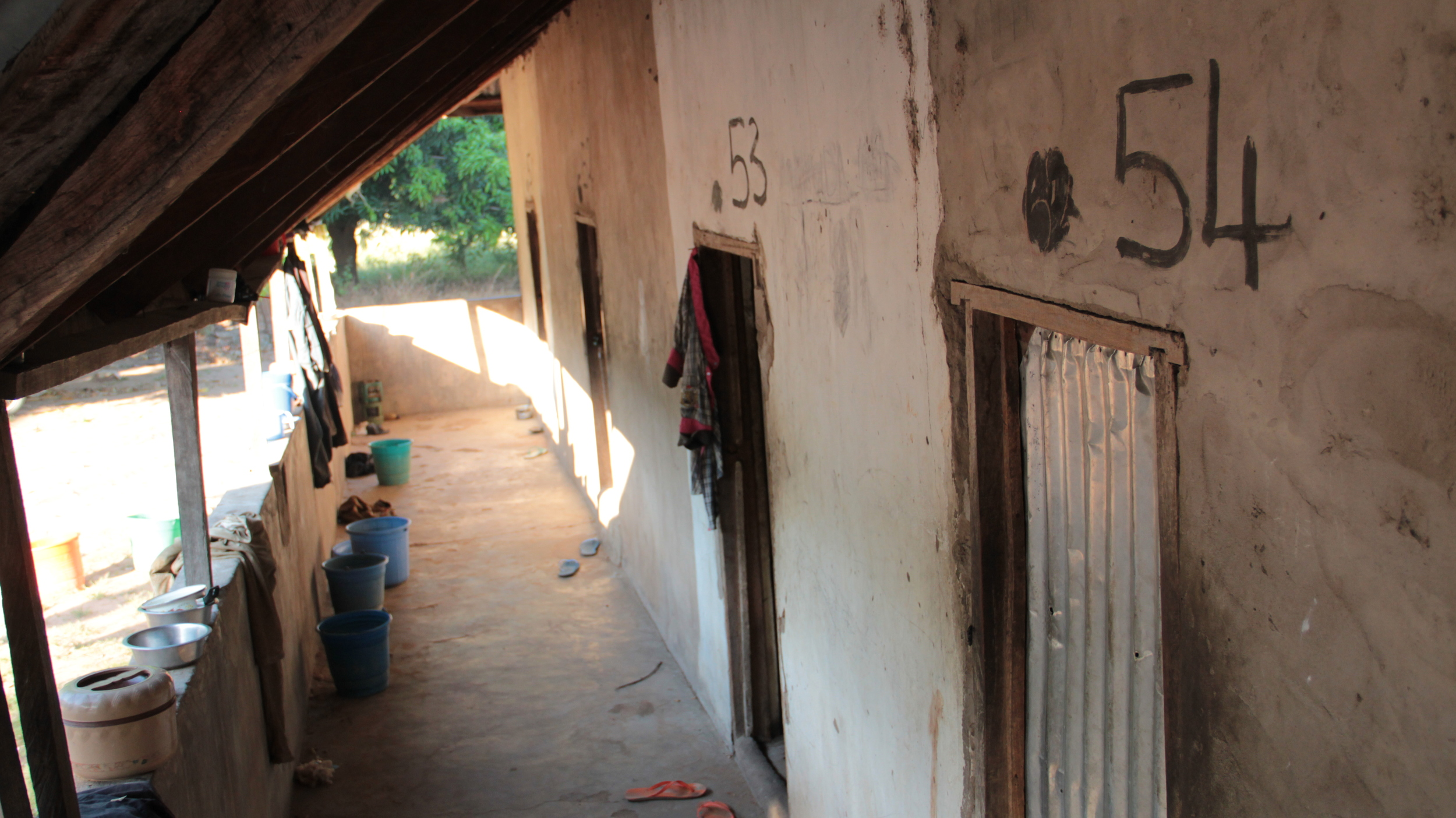 "Veranda of ""the monastery"".  Shoes, water pails, laundry and cooking pots collect here, like men's dorms anywhere."