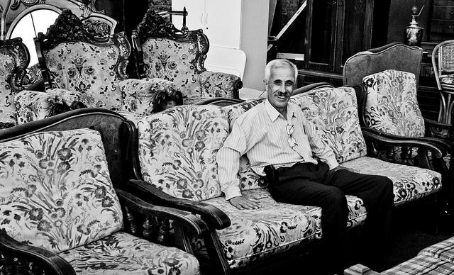 Ein møbelseljar sit i ein sofa til sal