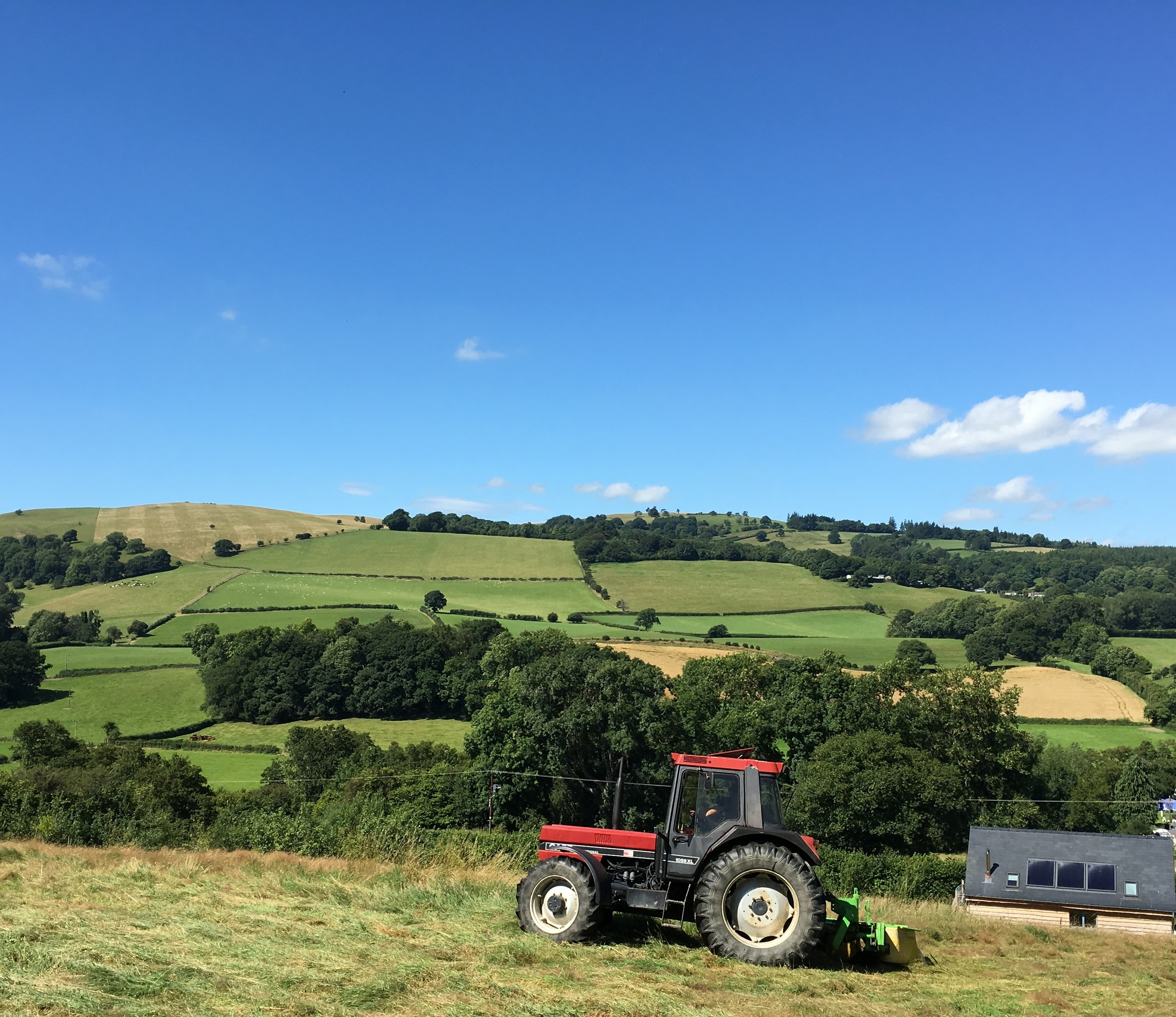 tractor tedding the hay with view of the hills in the background