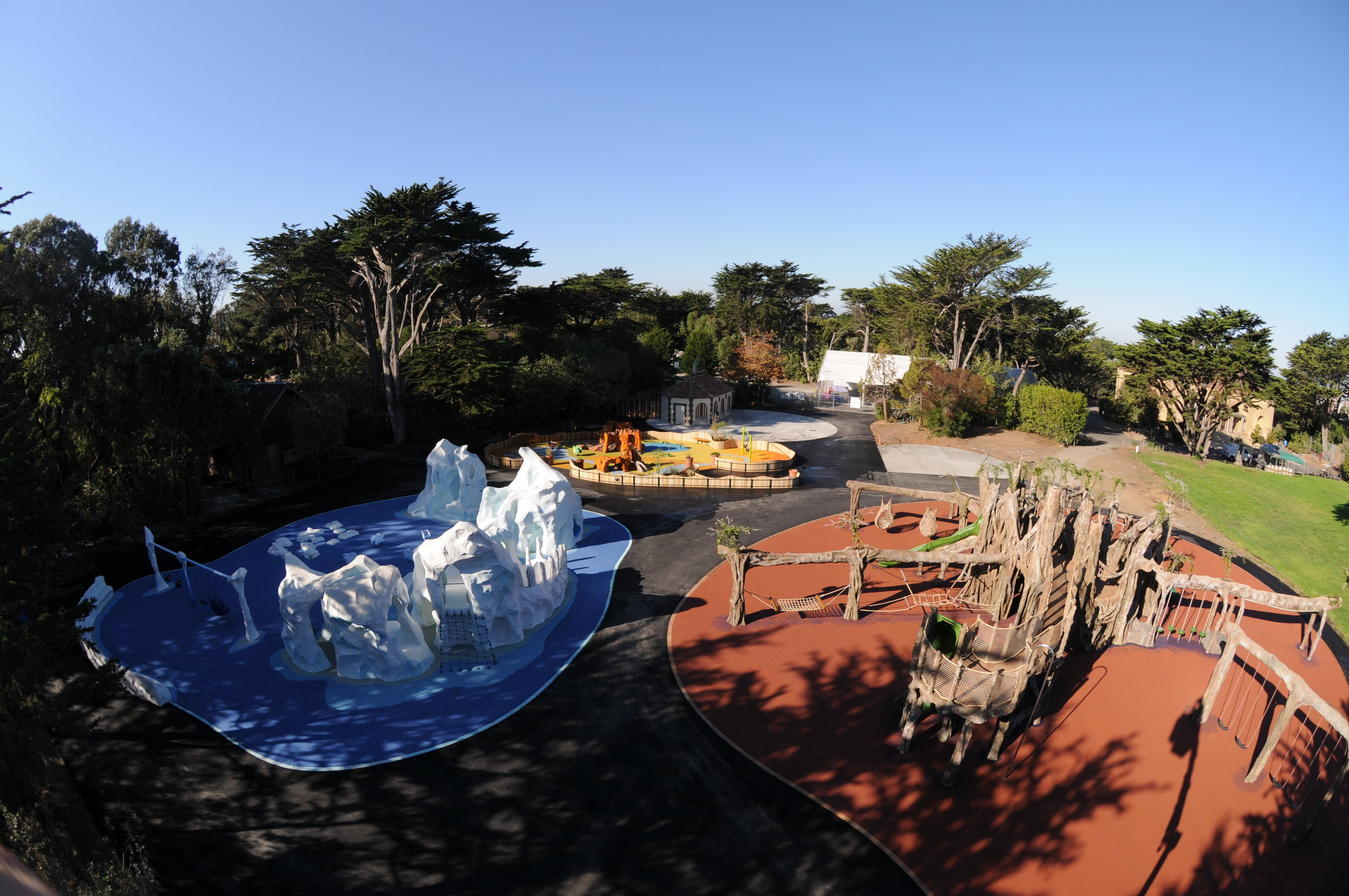 Nature inspired, unique playground with banyan tree climber, swings, slides, nest swingers, riverside play area; a riverside playground scene with natural redwood climbers, PIP rubber surfacing, and sand pit; natural sculpted concrete ice burg climber with ADA accessible swings