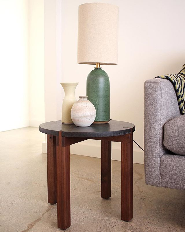 new Fig table in flamed black granite and black walnut, graced with @meredithmetcalfpottery 's beautiful work... #sidetable #madeinla #figsign #losangelesdesign #manufica