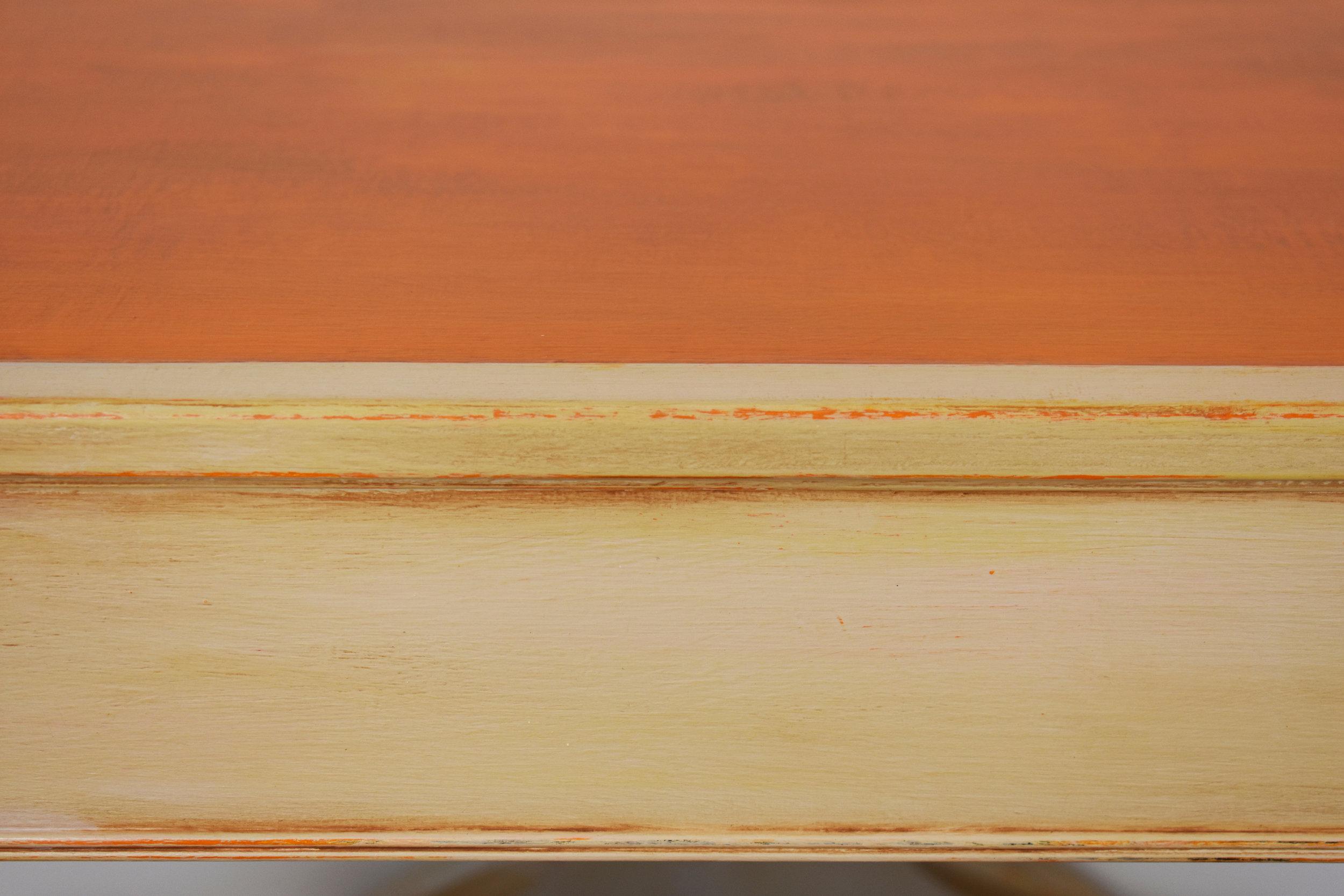 Off-white paint finish, distressing shows orange peeking through