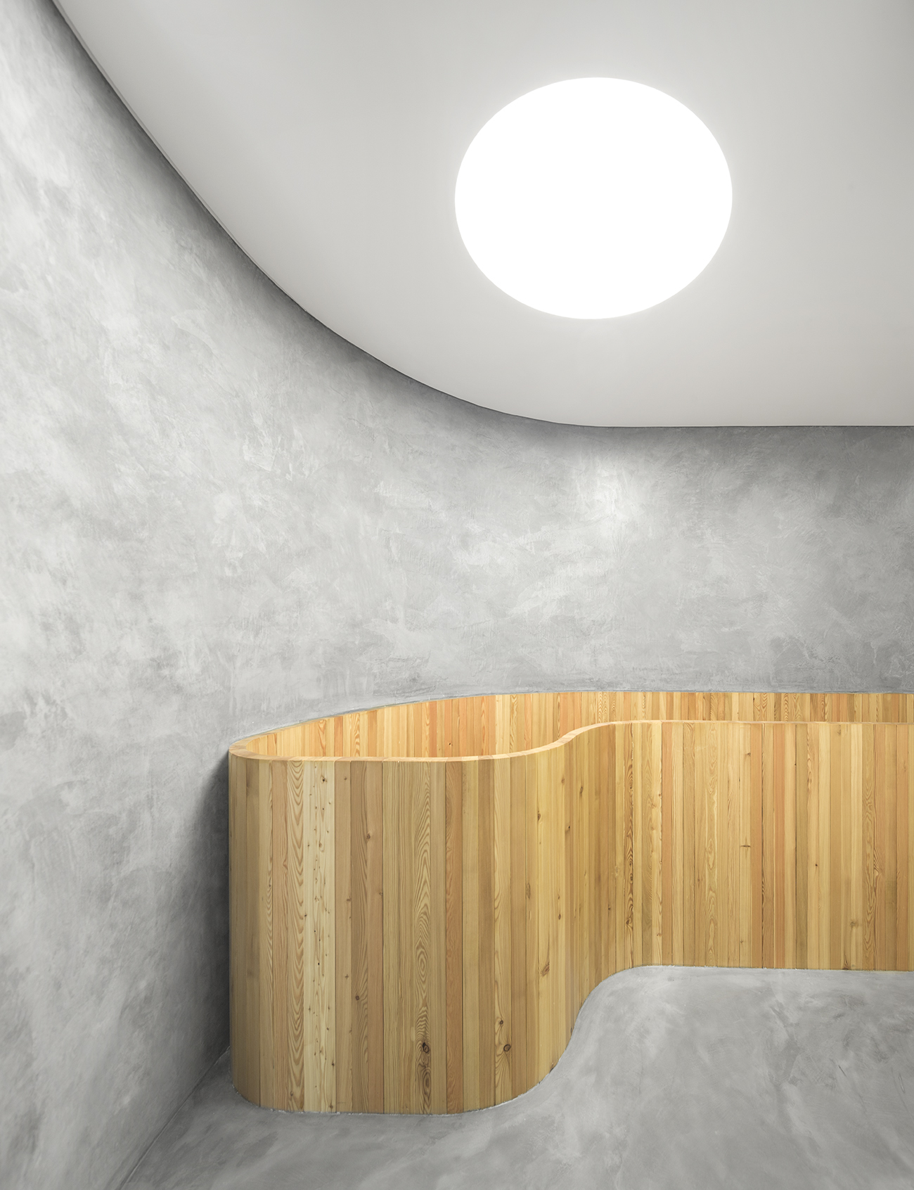 Wood stairs, glossy white walls mixed with textured concrete at DRDERM office by Atelier Central