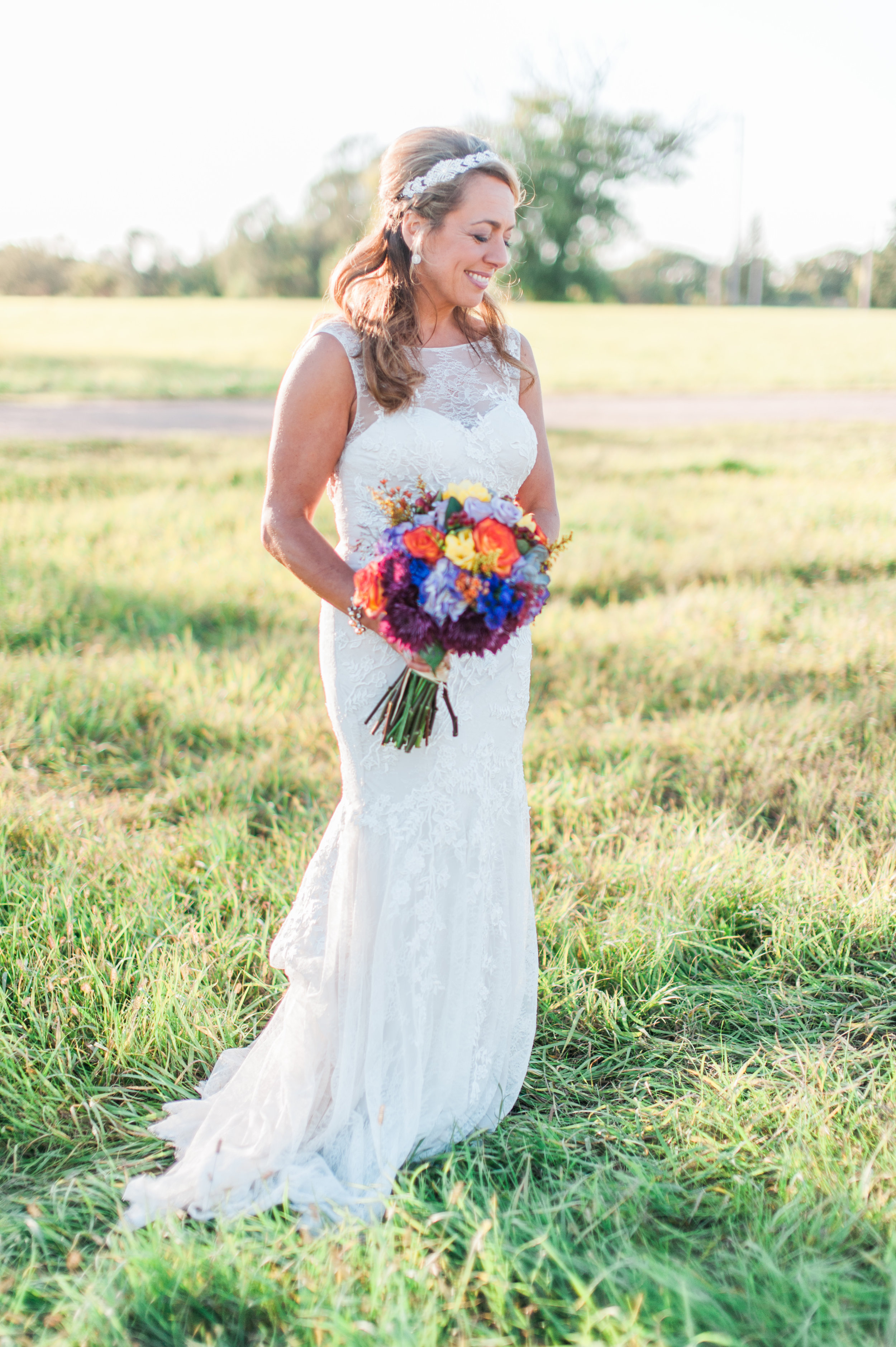A photograph by Samantha Weddings of a bride in a field near Omaha, Nebraska. Just outside of her outdoor wedding venue in Omaha.