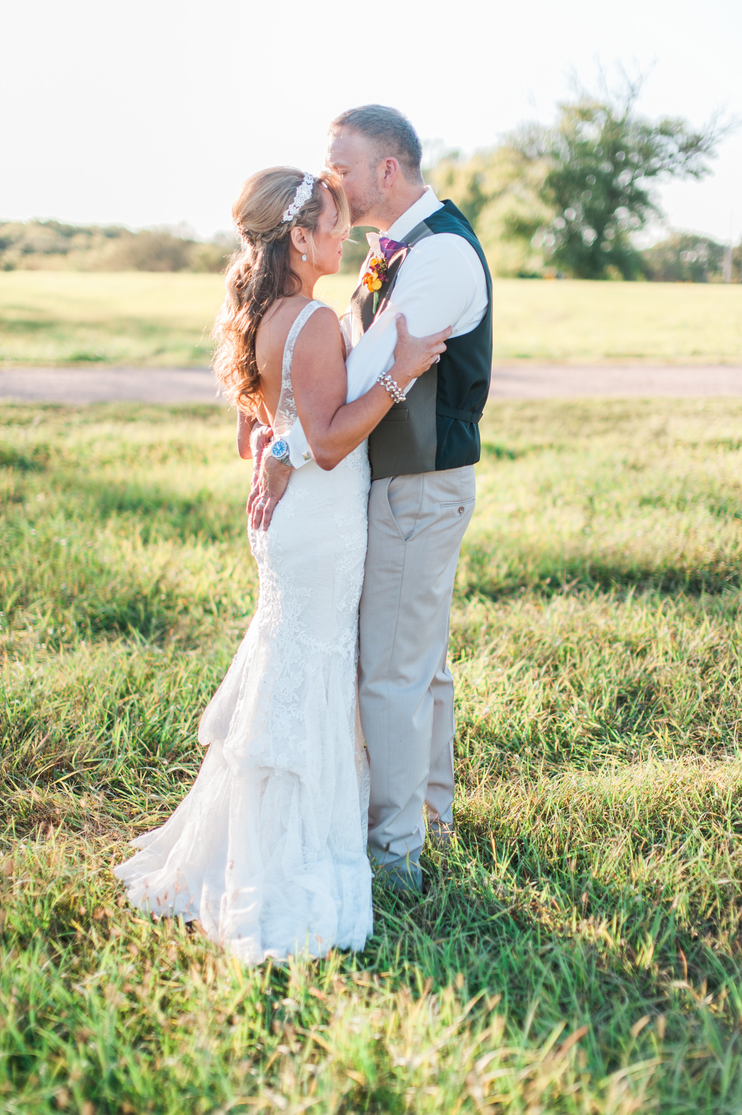 A photograph by Samantha Weddings of a bride and groom posing in a field at their outdoor wedding. The outdoor wedding venue had a field just to the west for us to use during pictures.