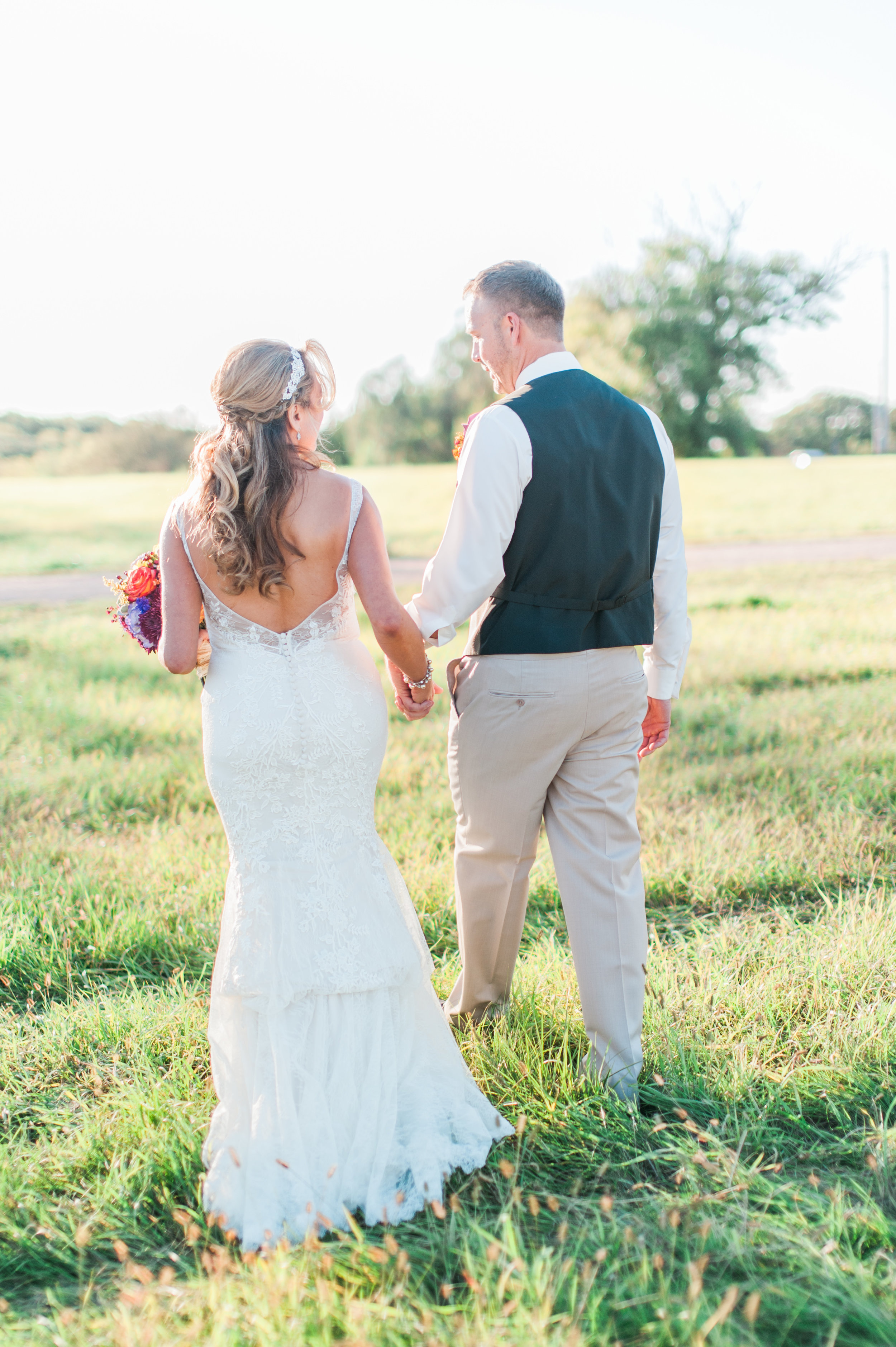 A photograph of a bride and groom by Samantha Weddings. The bride and groom are enjoying a walk in a field at the wedding venue Elk City hall in Omaha Nebraska.